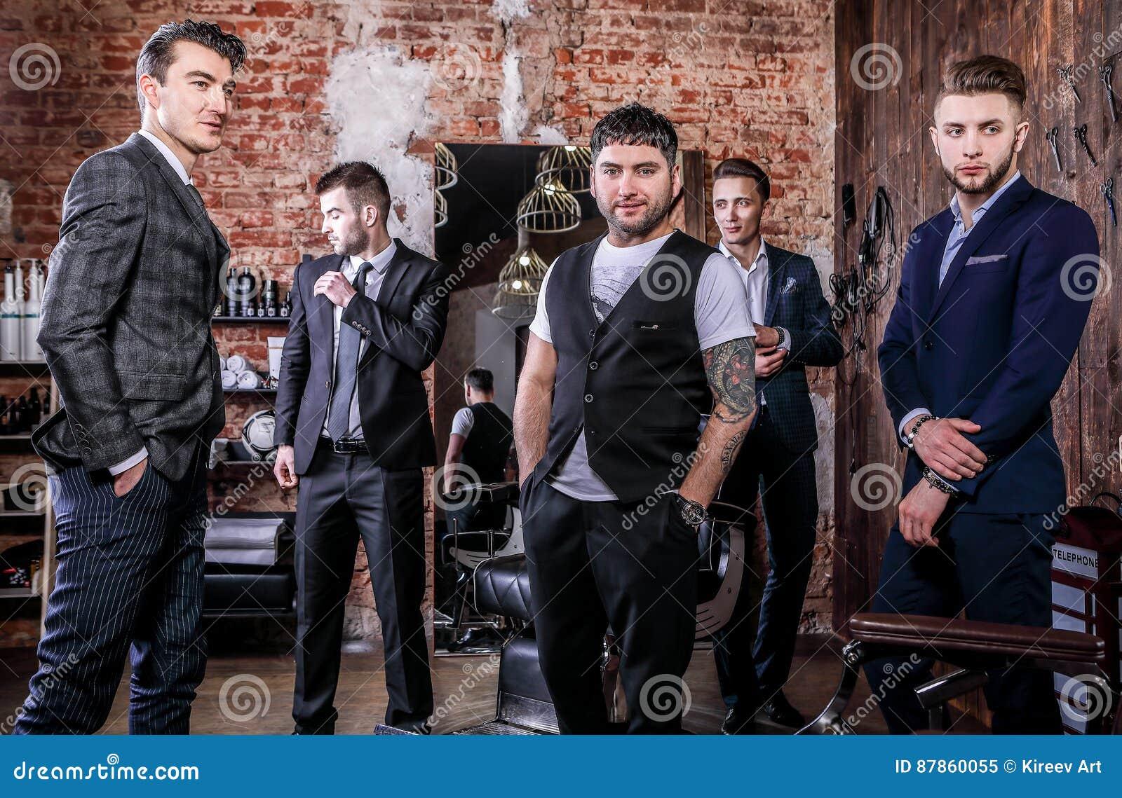Η ομάδα νέων κομψών θετικών ατόμων θέτει στο εσωτερικό του barbershop