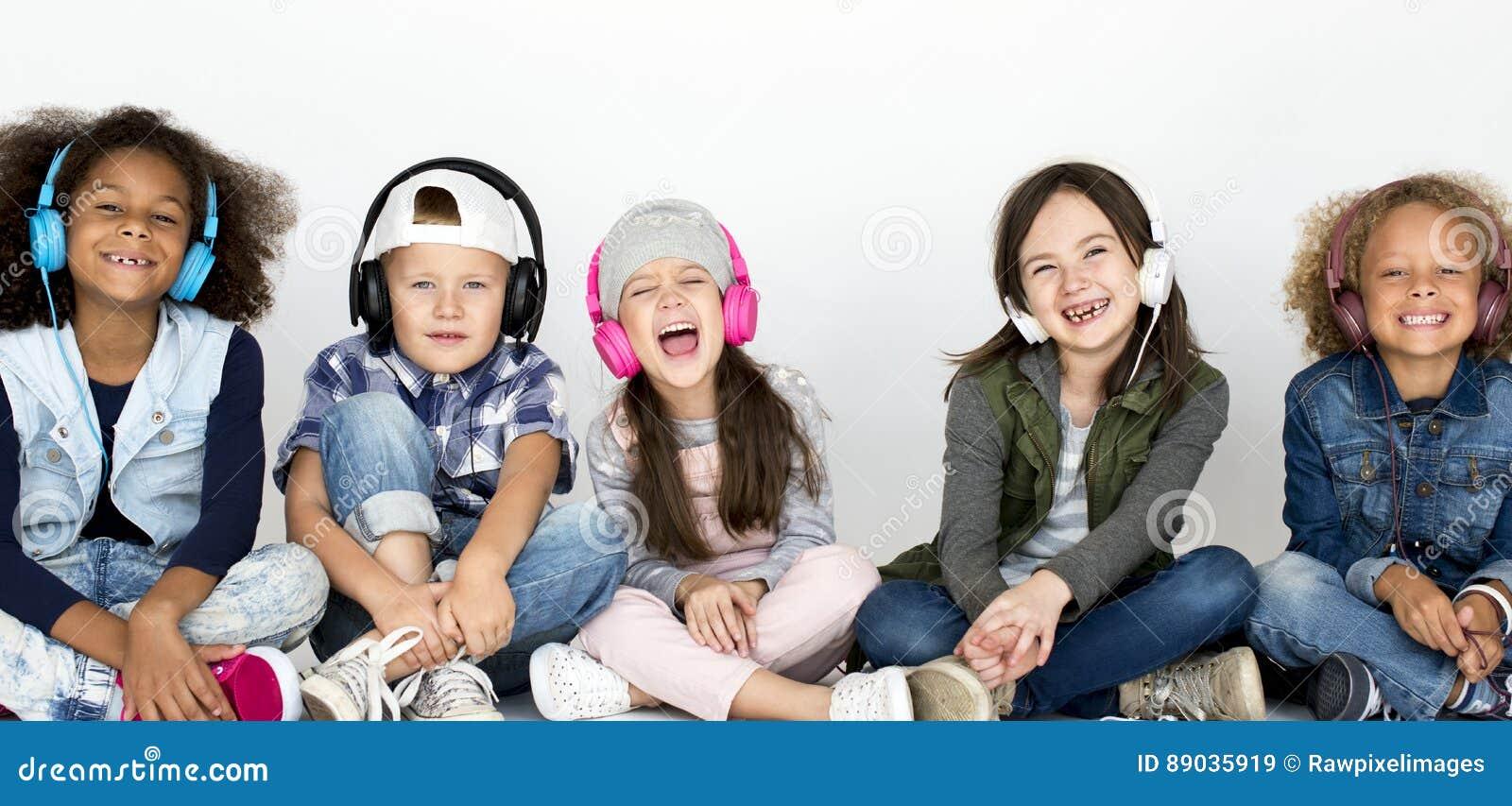 Η ομάδα παιδιών απολαμβάνεται τη μουσική από τα ακουστικά