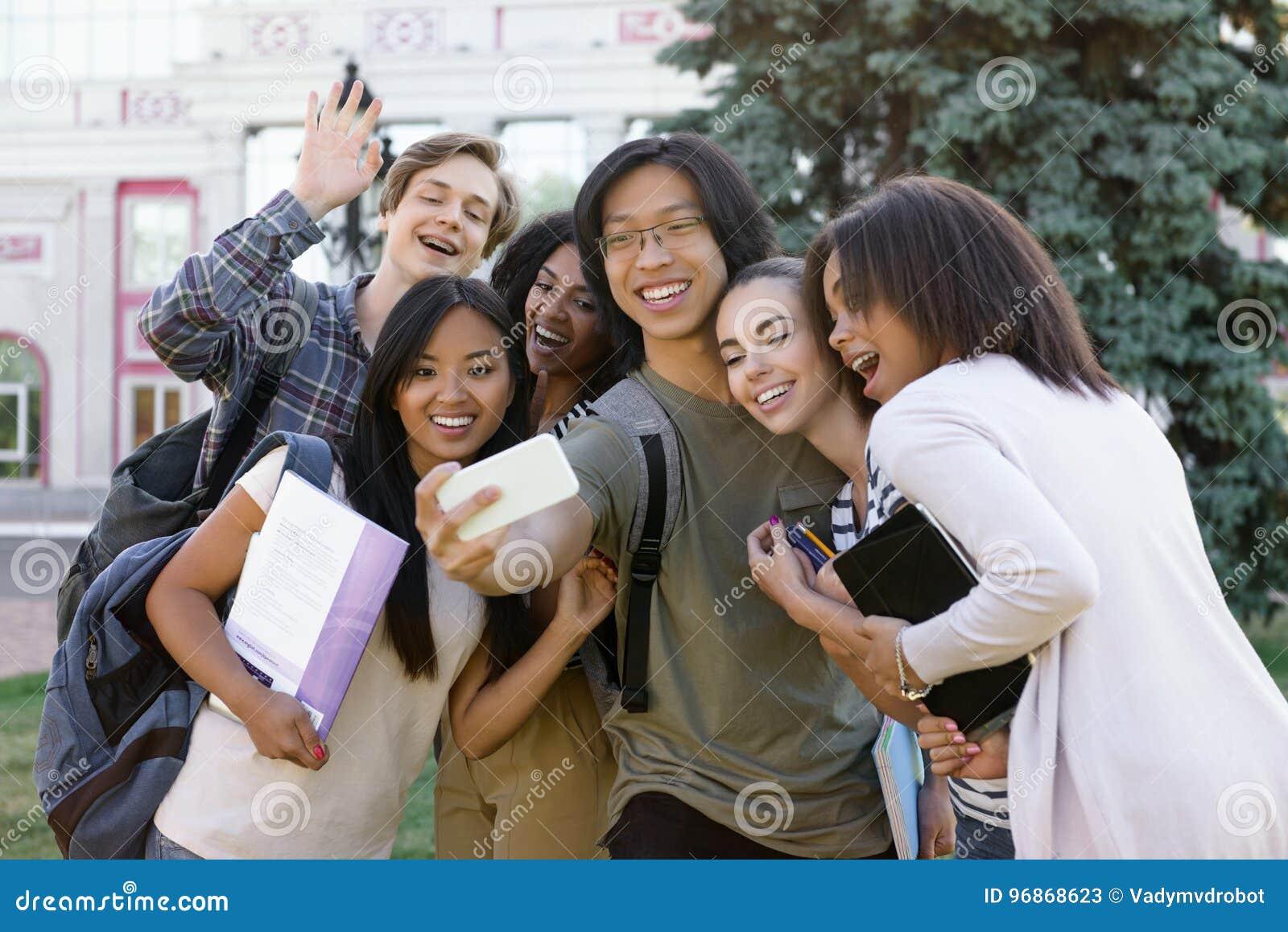 Η ομάδα Multiethnic νέων ευτυχών σπουδαστών κάνει selfie υπαίθρια