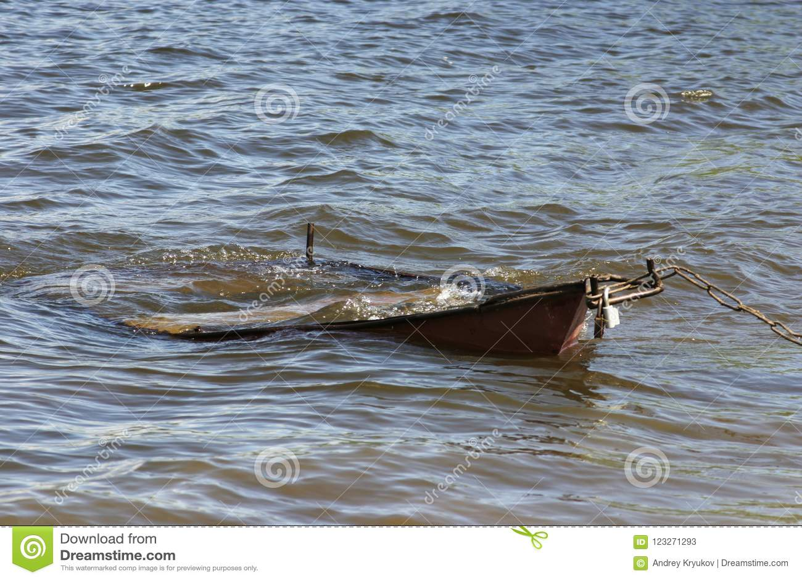 Η παλαιά βάρκα στο νερό έδεσε με την αλυσίδα σιδήρου με την κλειδαριά στην ακτή