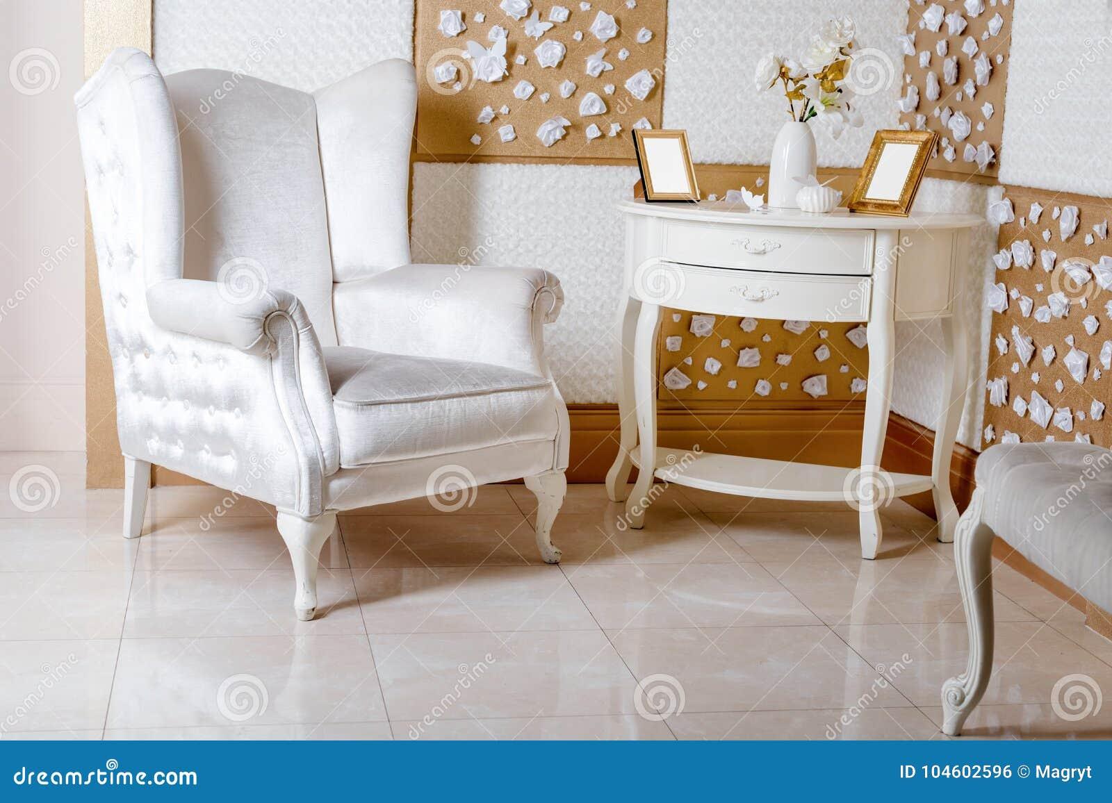 η παλαιά πολυθρόνα χάρασε την εσωτερική πολυτέλεια Πολυτελής άσπρη πολυθρόνα, χαρασμένα αντίκα έπιπλα, κλασική εσωτερική λεπτομέρ
