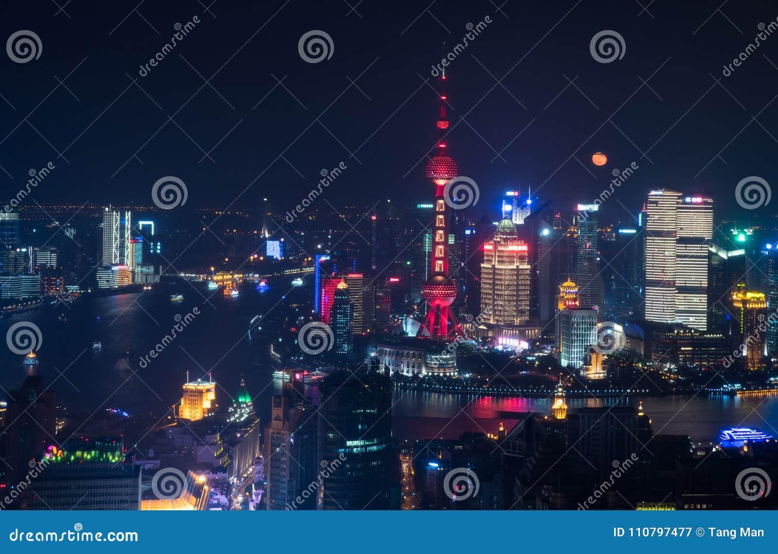 Η πανσέληνος αυξάνεται πίσω από τον ορίζοντα Pudong