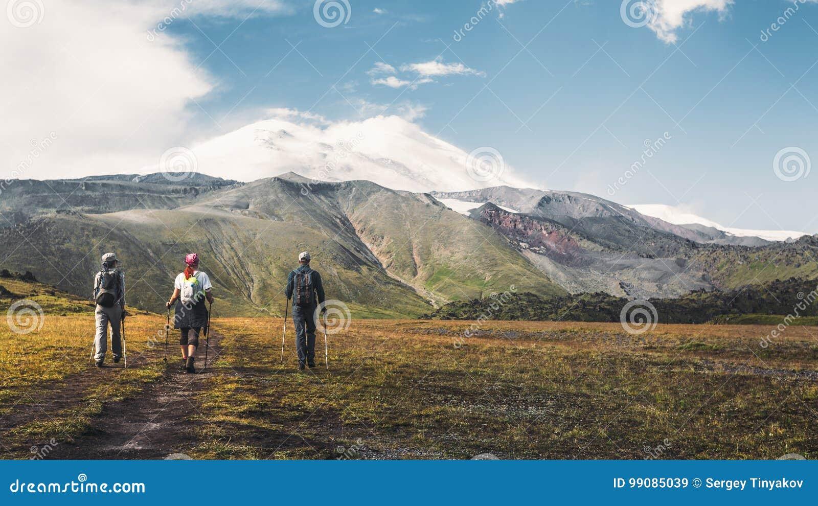 Η πεζοπορία ομάδα πηγαίνει να τοποθετήσει Elbrus, οπισθοσκόπο Έννοια έννοιας τρόπου ζωής εμπειρίας προορισμού ταξιδιού