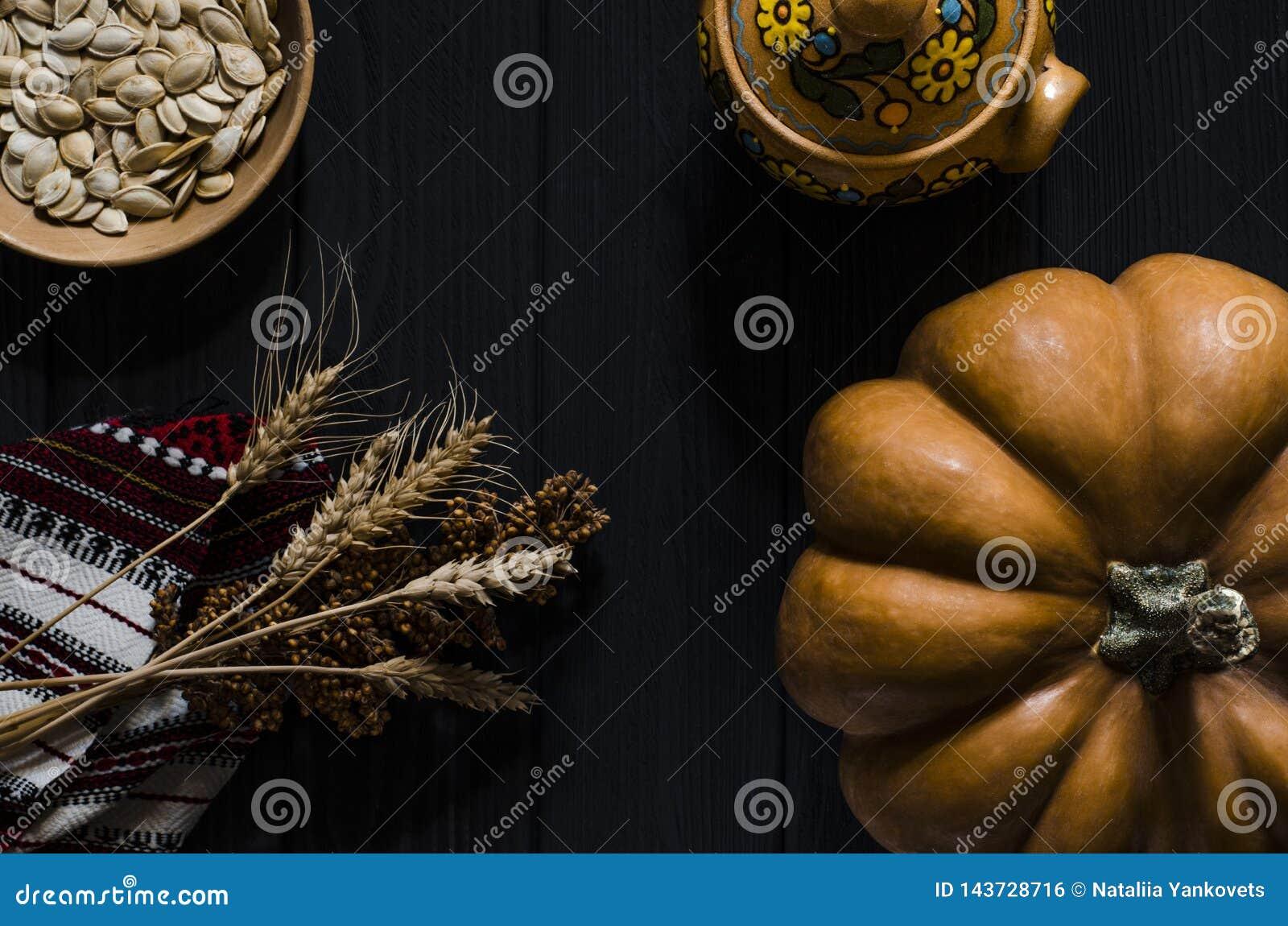 Η πορτοκαλιά κολοκύθα, οι σπόροι κολοκύθας και τα αυτιά σίτου βρίσκονται σε ένα μαύρο ξύλινο υπόβαθρο