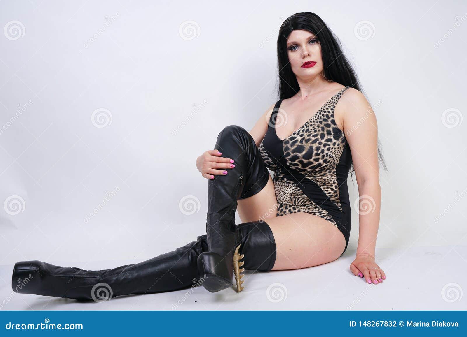 Η προκλητική επικίνδυνη γυναίκα brunette στις υψηλές μπότες μηρών μαγιό και δέρματος λεοπαρδάλεων με το σκελετό βάζει τακούνια στ