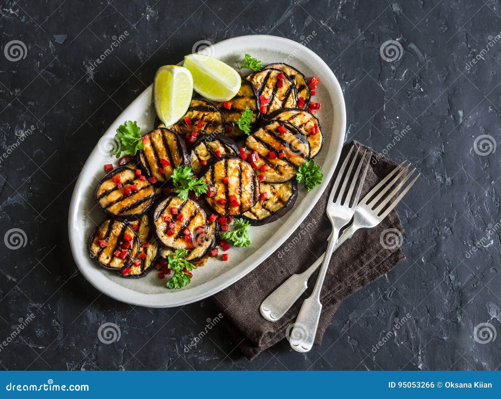 Η σάλτσα και η πιπερόριζα σόγιας μαρινάρισαν την ψημένη στη σχάρα μελιτζάνα σε ένα σκοτεινό υπόβαθρο, τοπ άποψη Εύγευστο χορτοφάγ