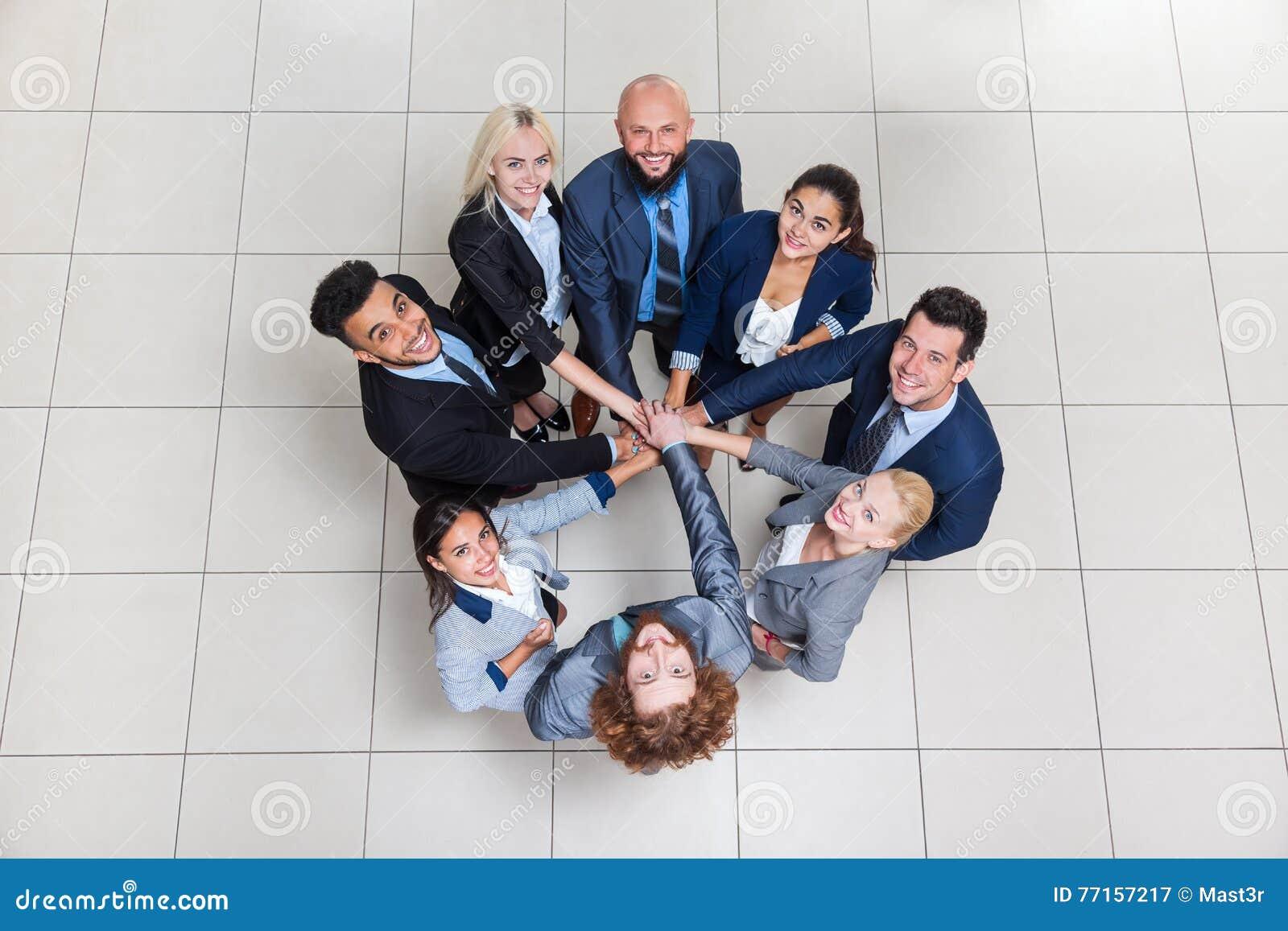 Η στάση ομάδας επιχειρηματιών στον κύκλο, ομάδα Businesspeople που βάζει το σωρό χεριών τους κοιτάζει επάνω στη συνεργασία ομαδικ