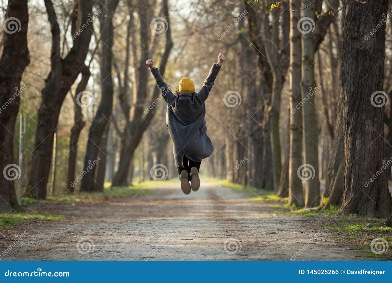 Η συγκινημένη νέα γυναίκα πηδά με τα όπλα που αυξάνονται επάνω