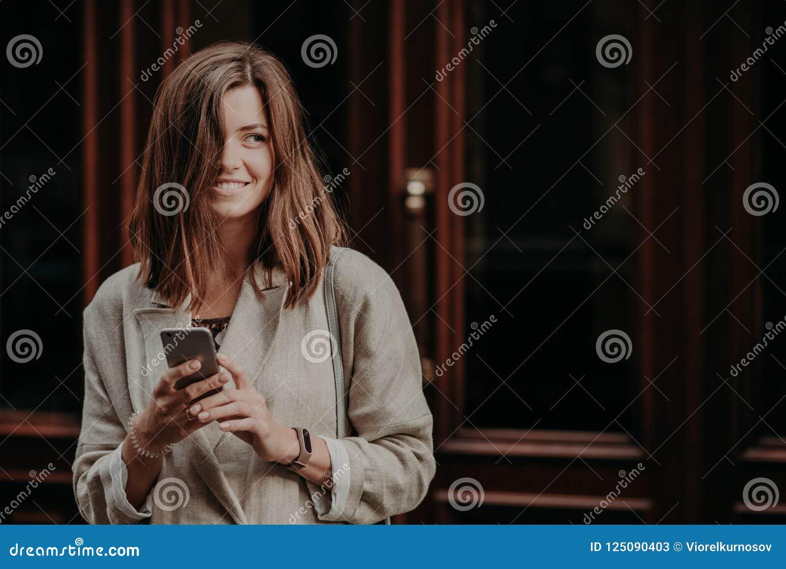 Η συναισθηματική ευχαριστημένη ευτυχής νέα γυναίκα brunette με τη σκοτεινή τρίχα, κινητό τηλέφωνο χρήσεων για τα μηνύματα, έντυσε