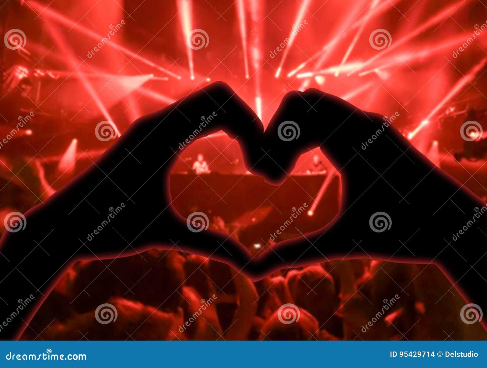 Η συναυλία μουσικής, χέρια που αυξήθηκαν με μορφή της καρδιάς για τη μουσική, θόλωσε το πλήθος και τους καλλιτέχνες στη σκηνή στο