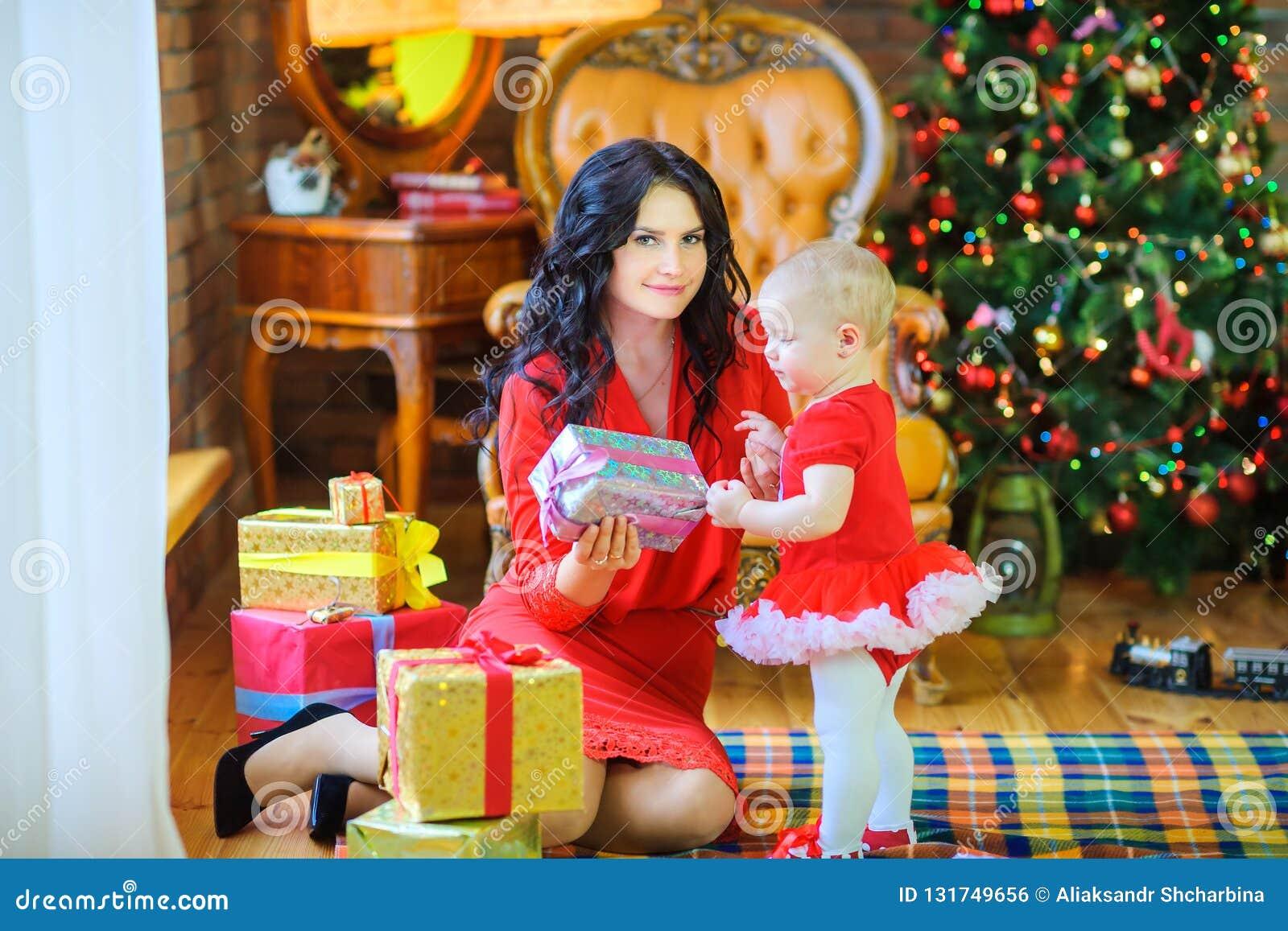 Η συνεδρίαση μητέρων στο πάτωμα κοντά στο χριστουγεννιάτικο δέντρο δίνει ένα δώρο στην αγαπημένη κόρη της