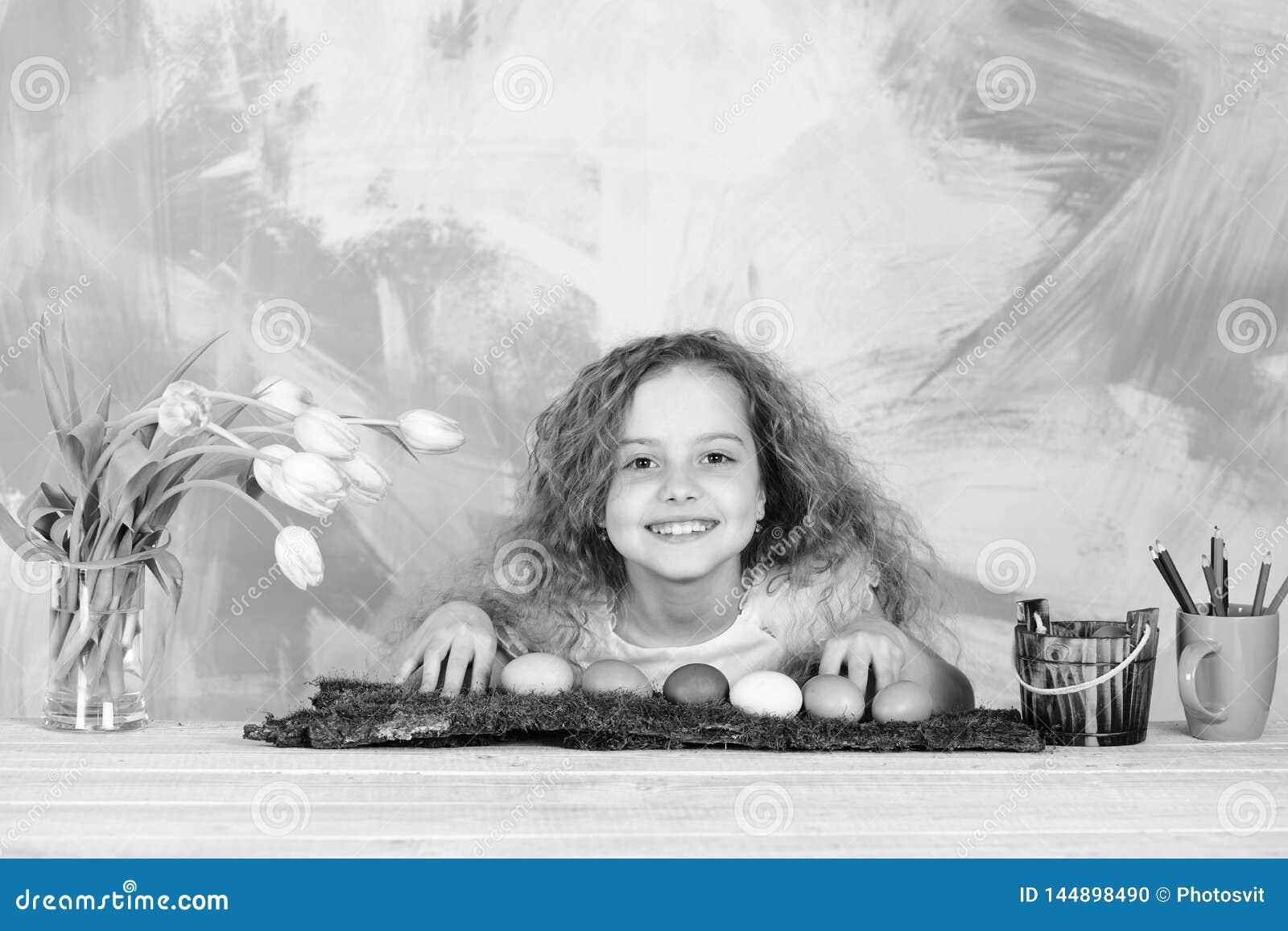 Ευτυχές κορίτσι Πάσχας με τα μολύβια, τα ζωηρόχρωμα αυγά και τα λουλούδια τουλιπών
