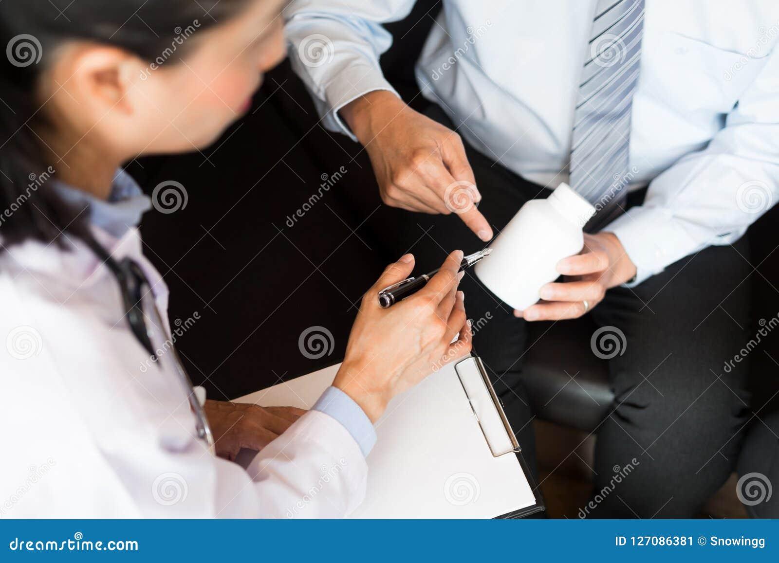 Η ταμπλέτα εκμετάλλευσης χεριών γιατρών του φαρμάκου και εξηγεί στον ασθενή στο ho