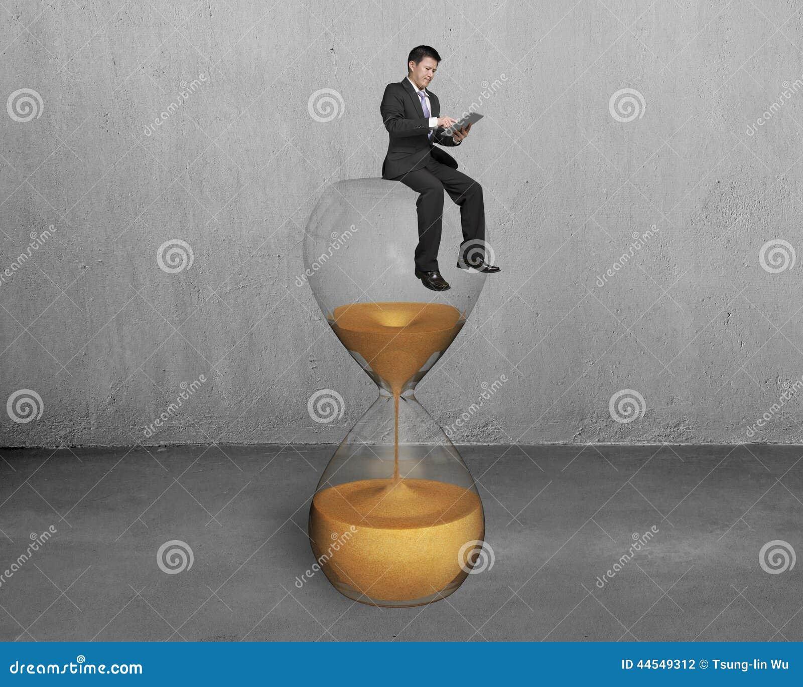Η ταμπλέτα χρήσης ατόμων και κάθεται στην κλεψύδρα