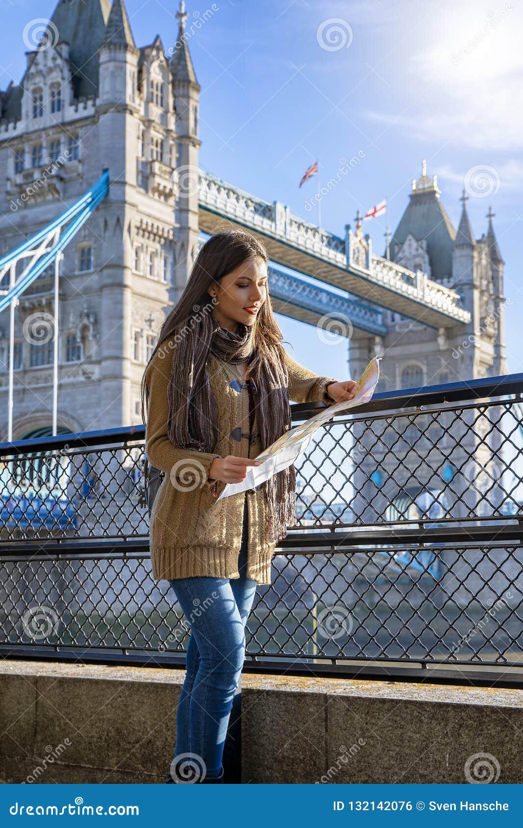 Η ταξιδιωτική γυναίκα κρατά έναν χάρτη μπροστά από τη γέφυρα Λονδίνο πύργων