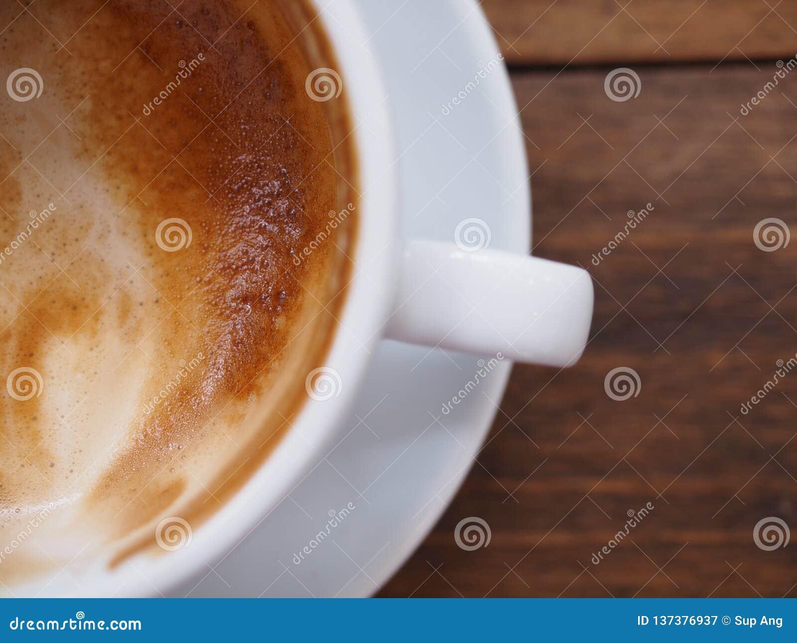 Η τοπ άποψη και κλείνει επάνω τον καφέ στο άσπρο φλυτζάνι στον ξύλινο πίνακα
