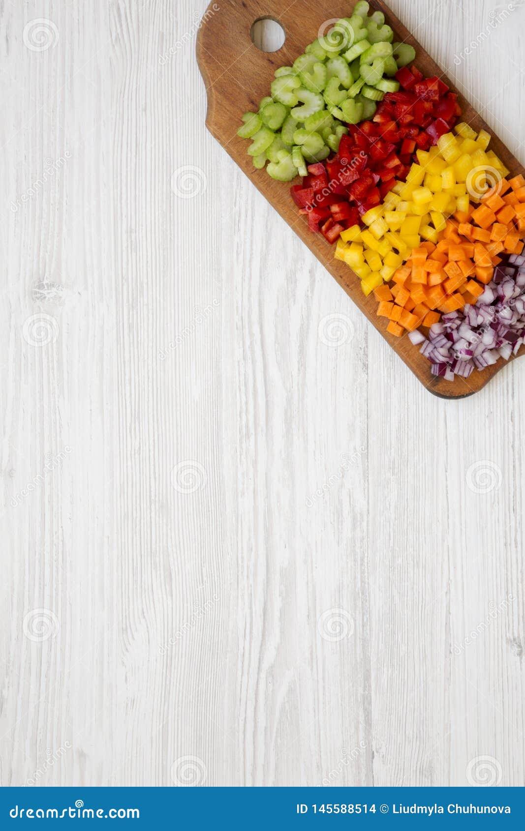 Η τοπ άποψη, τεμαχισμένο καρότο φρέσκων λαχανικών, σέλινο, κόκκινο κρεμμύδι, χρωμάτισε τα πιπέρια που τακτοποιήθηκαν στον τέμνοντ