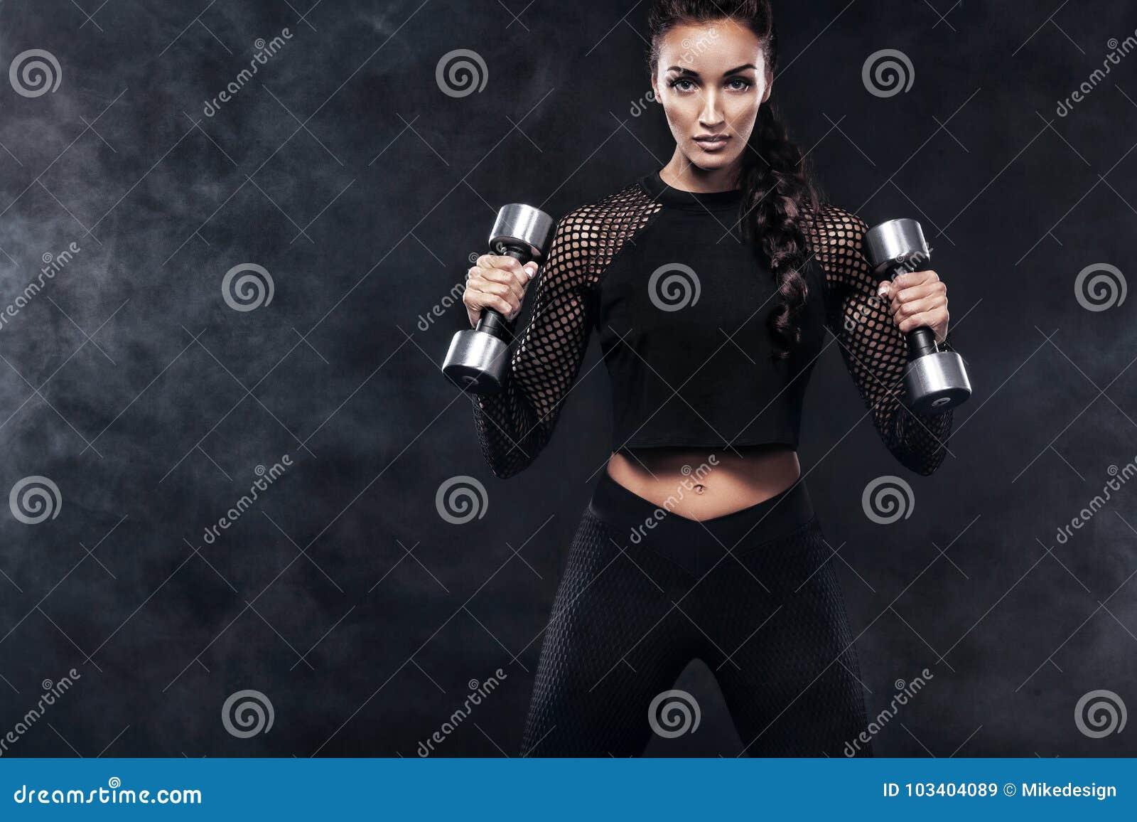 Η φίλαθλη όμορφη γυναίκα με τους αλτήρες κάνει την ικανότητα ασκώντας στο μαύρο υπόβαθρο για να μείνει κατάλληλη