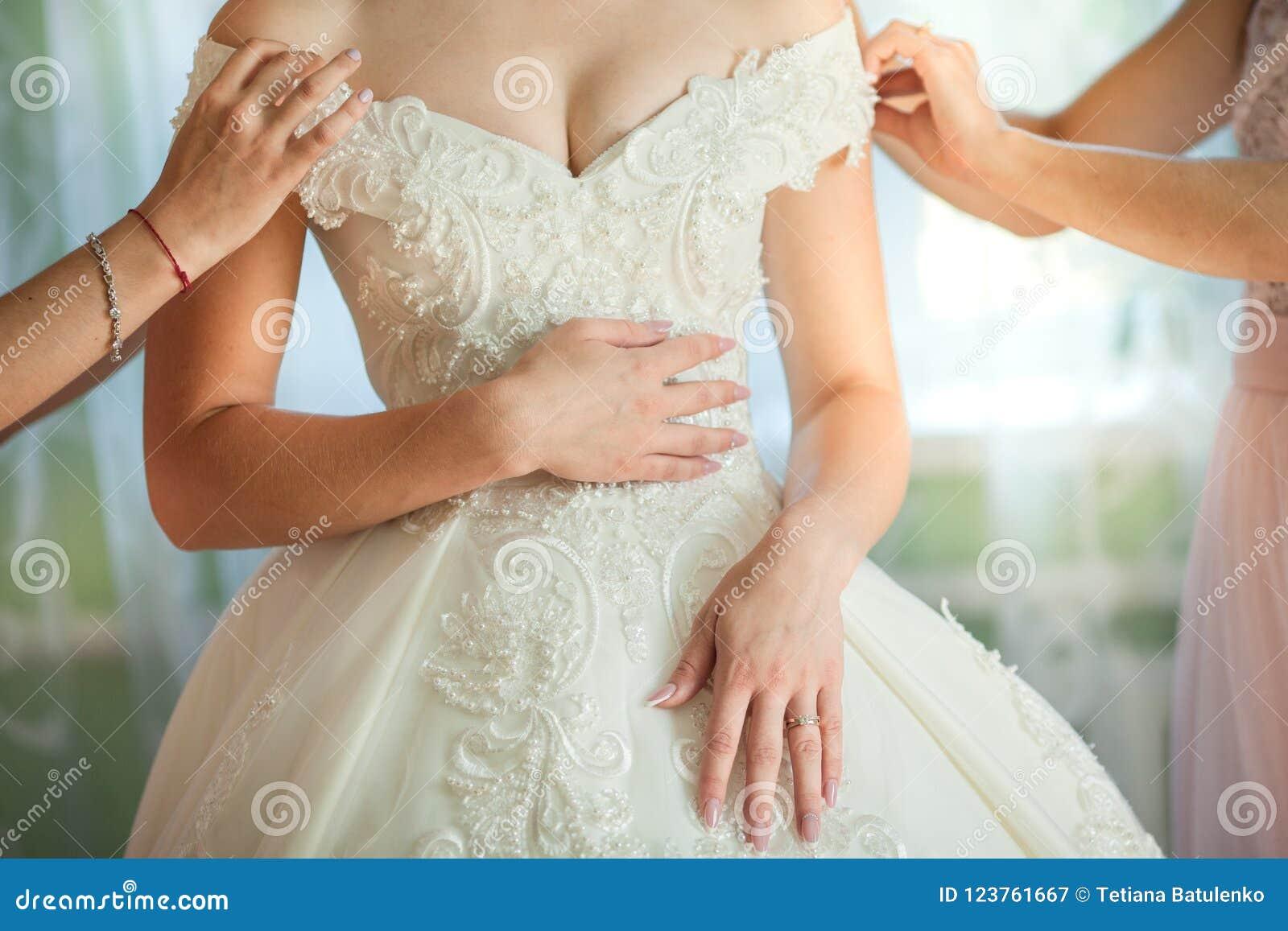 Η φίλη νυφών ` s βοηθά το φόρεμα νυφών επάνω το γαμήλιο φόρεμά της