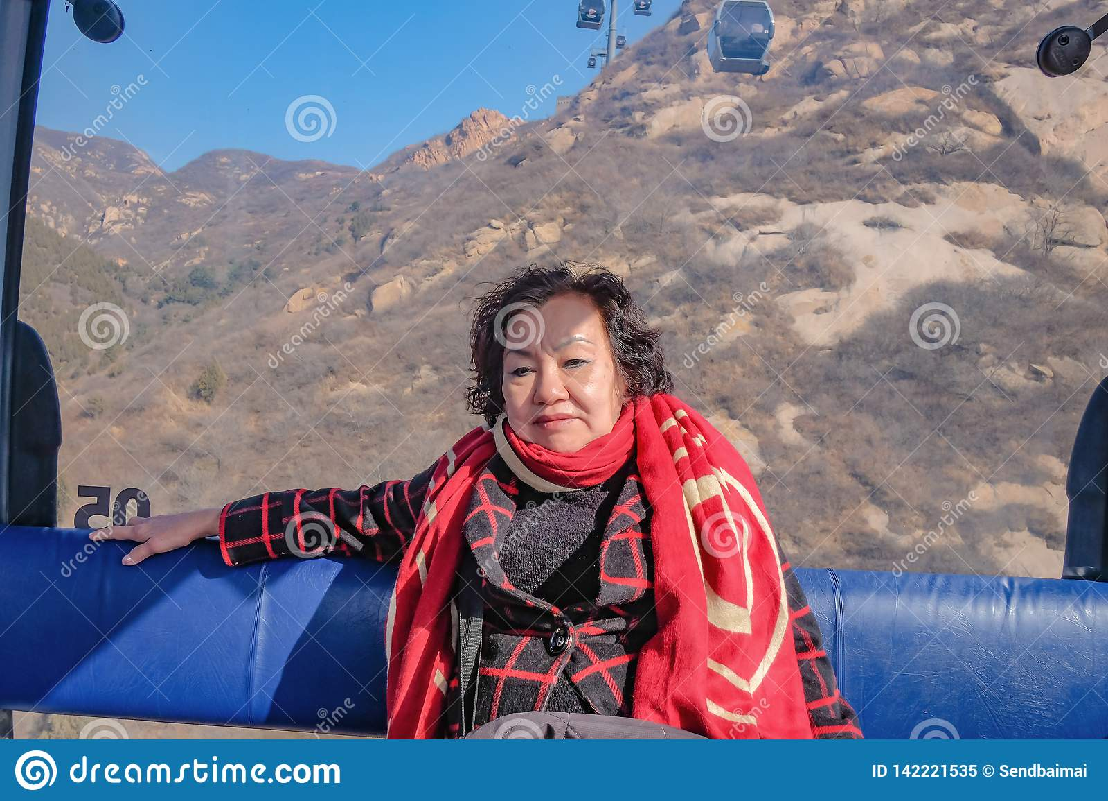 Η φωτογραφία πορτρέτου της ανώτερης ασιατικής ταξιδιωτικής συνεδρίασης γυναικών στο τελεφερίκ διασχίζει το βουνό στο Σινικό Τείχο