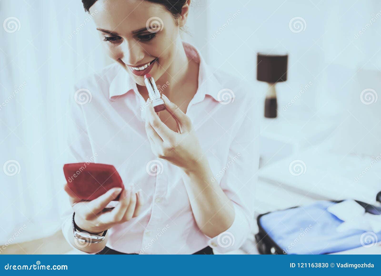 Η χαμογελώντας γυναίκα κοιτάζει στον καθρέφτη και χρωματίζει τα χείλια της