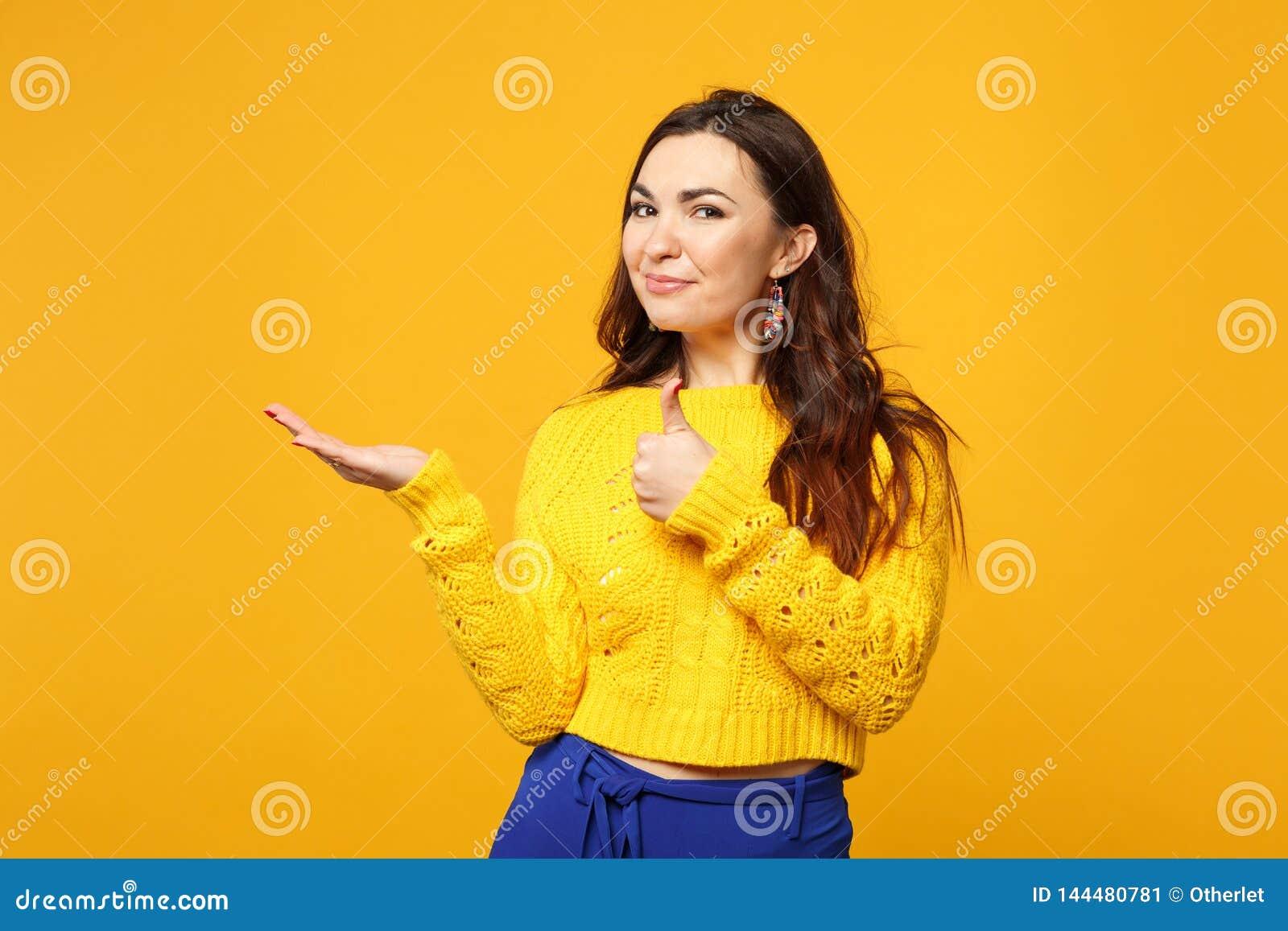 Η χαμογελώντας νέα γυναίκα στο πουλόβερ, μπλε παντελόνι που φαίνεται κάμερα, δείχνοντας το χέρι κατά μέρος, που παρουσιάζει αντίχ