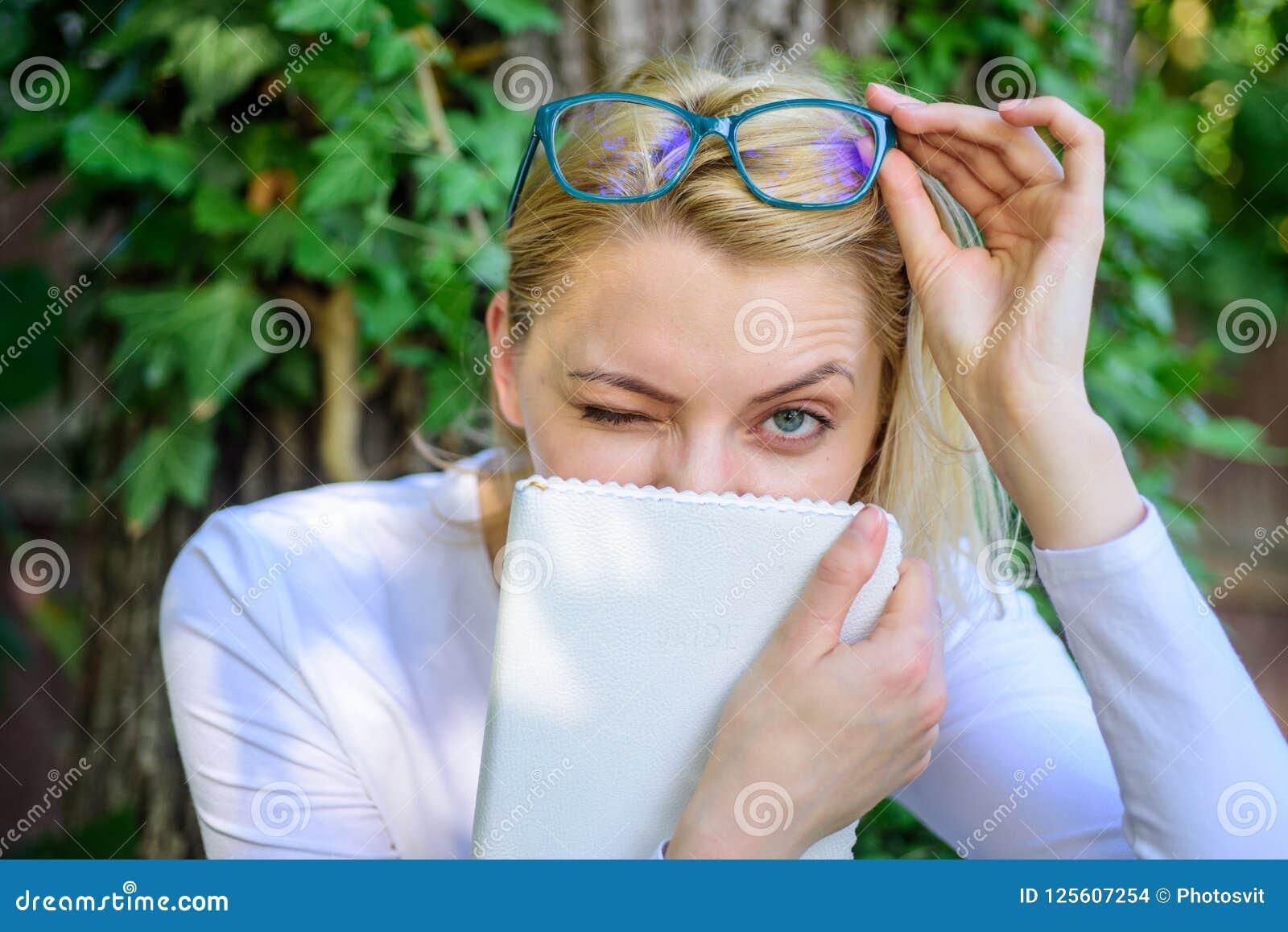 Η χαριτωμένη βιβλιόψειρα eyeglasses απολαμβάνει κάθε κεφάλαιο Χαλάρωση σπουδαστών βιβλιοψειρών με το πράσινο υπόβαθρο φύσης βιβλί