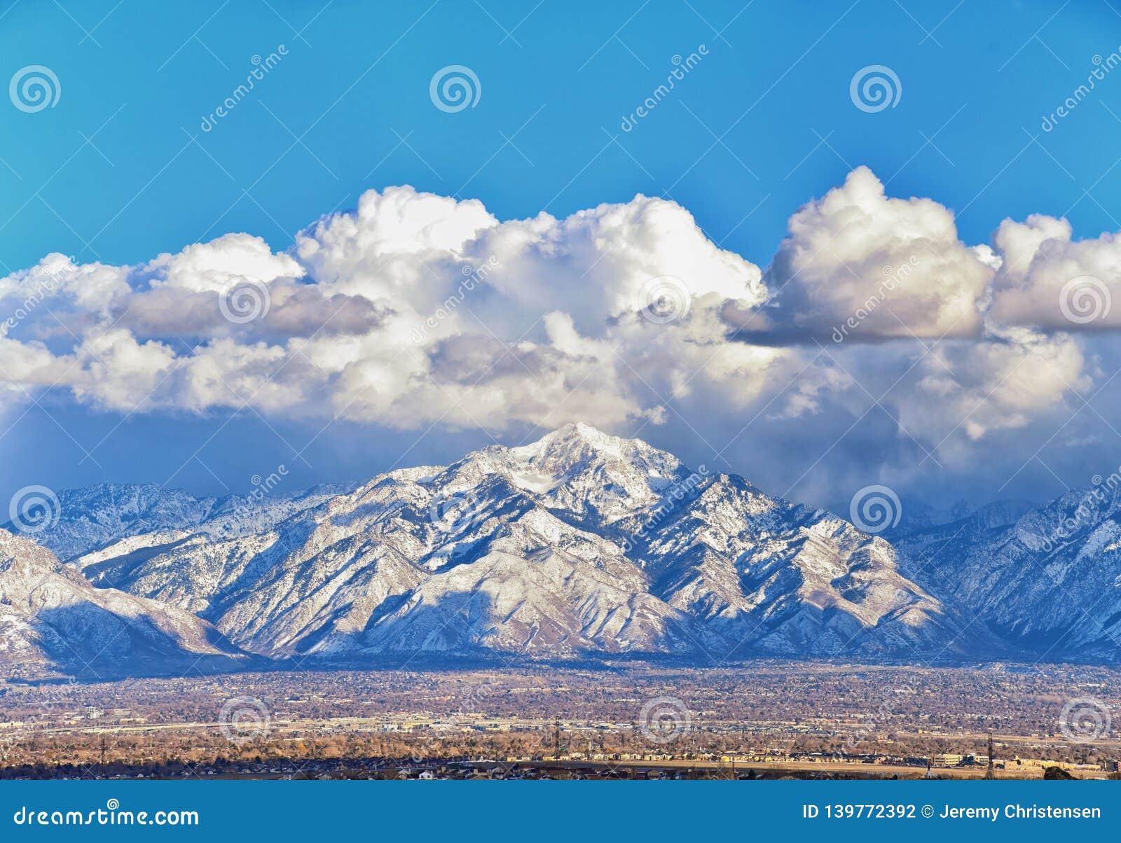 Η χειμερινή πανοραμική άποψη του χιονιού κάλυψε τα μπροστινά δύσκολα βουνά Wasatch, την κοιλάδα του Γκρέιτ Σωλτ Λέηκ και Cloudsca