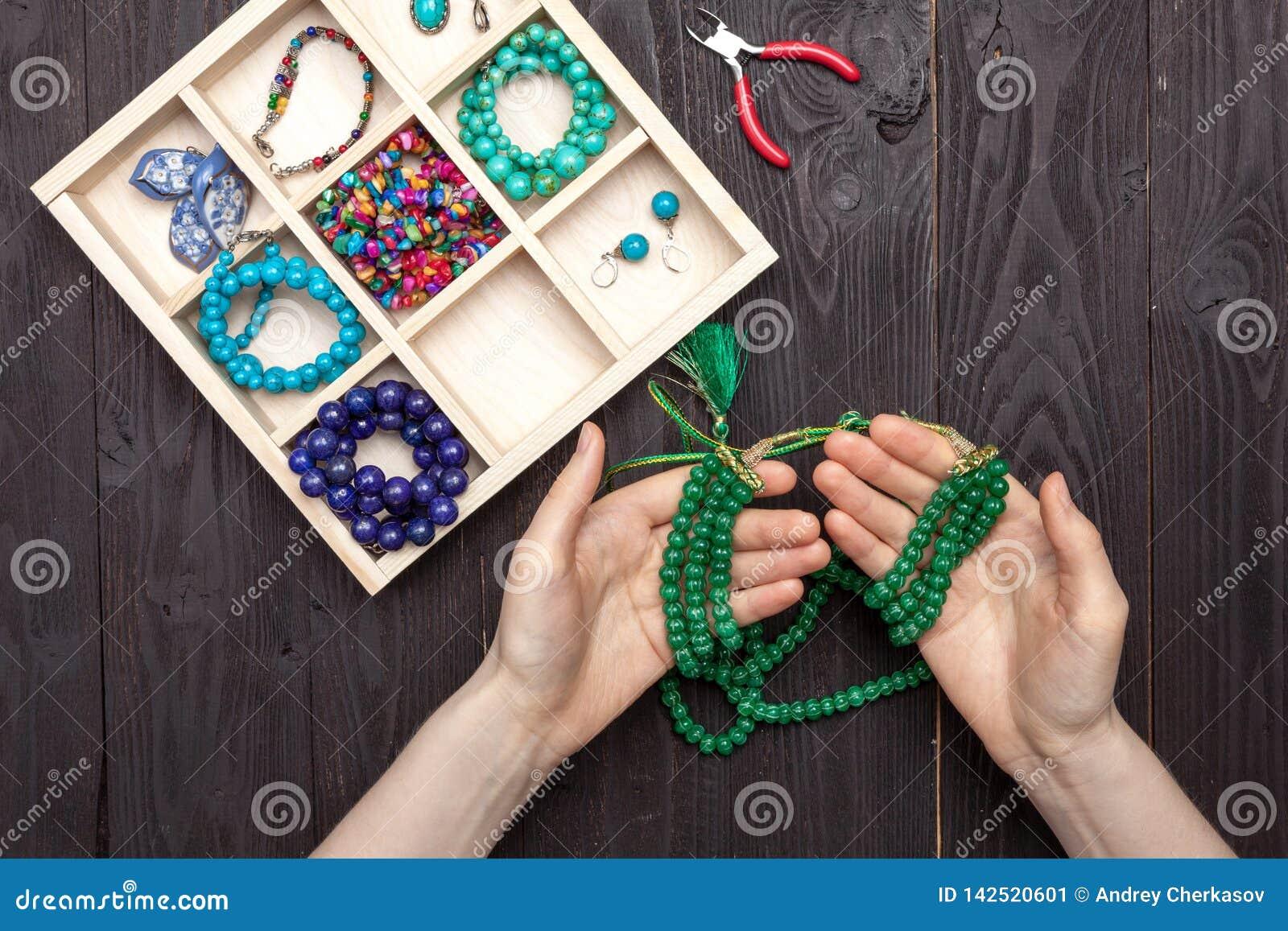 Η χειροτεχνία στο σπίτι, το κορίτσι κάνει τα χέρια κοσμήματος στον πίνακα