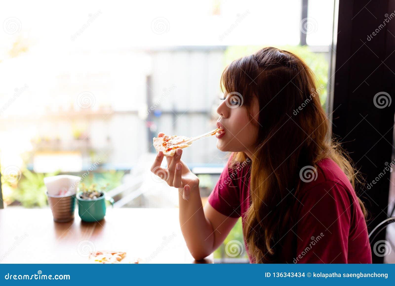 Η όμορφη ασιατική γυναίκα αγαπά να φάει την πίτσα και να απολαύσει το γούστο του τυριού μοτσαρελών τόσο πολύ Η γοητεία της όμορφη