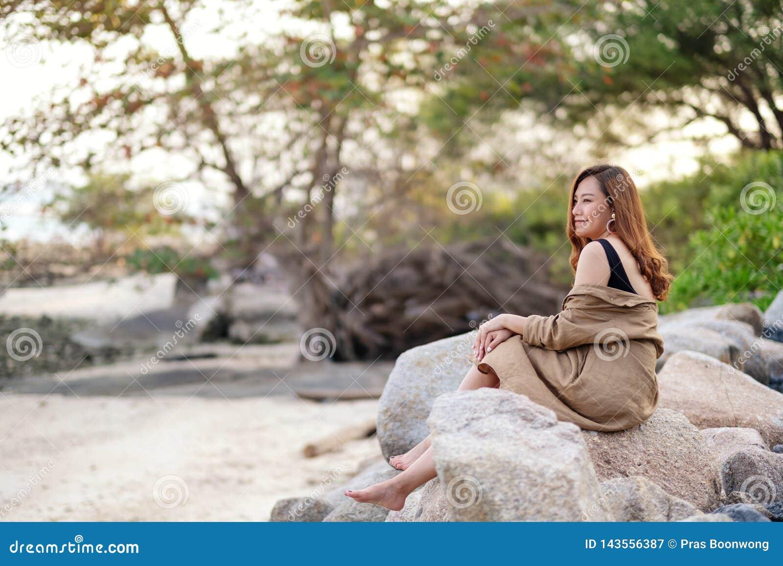 Η όμορφη ασιατική γυναίκα απολαμβάνει στο βράχο από την ακτή