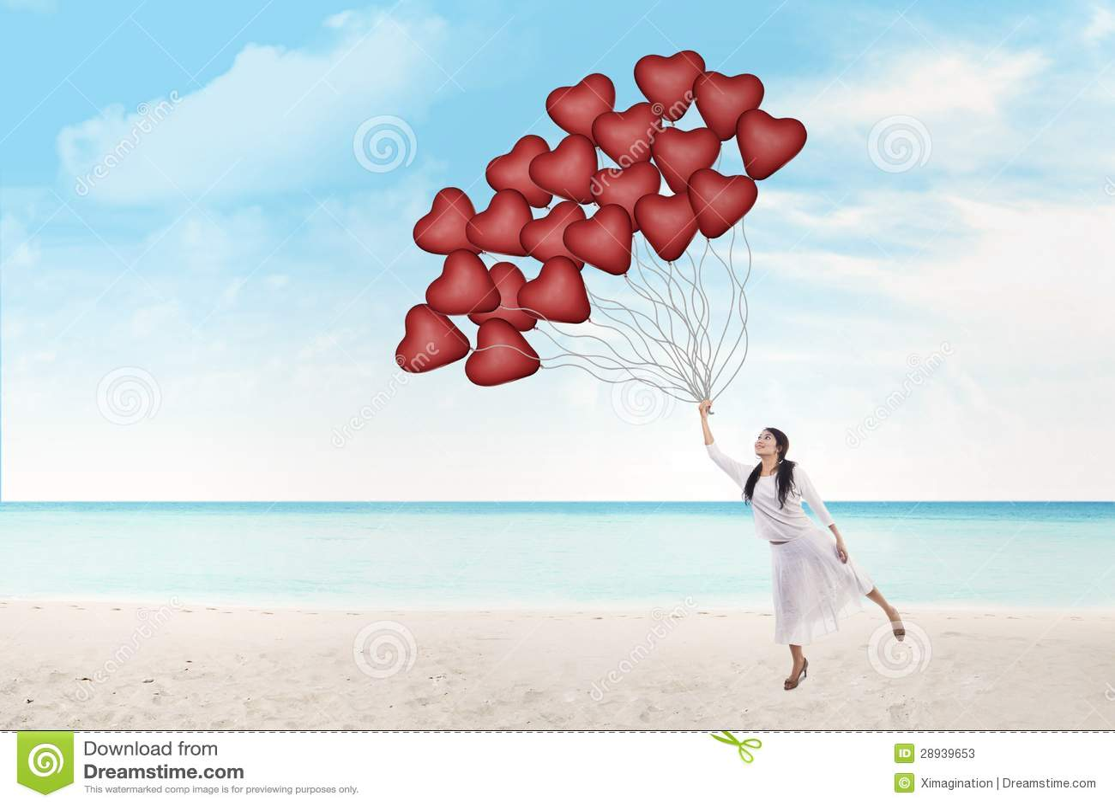 Η όμορφη γυναίκα κρατά τα μπαλόνια καρδιών