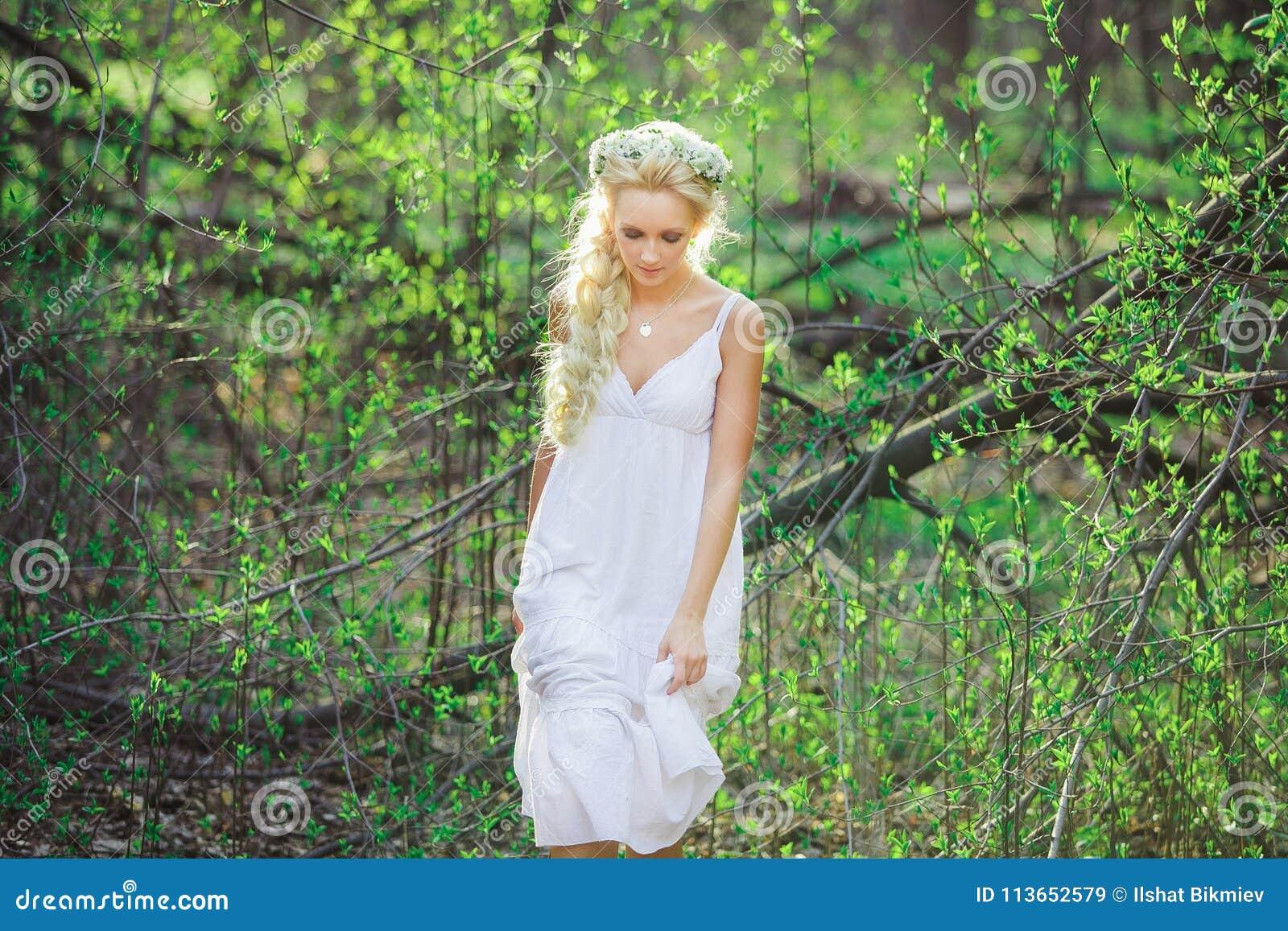 690a94543fad Η όμορφη γυναίκα στο άσπρο φόρεμα και το floral στεφάνι στο κεφάλι της  μεταξύ της άνθησης