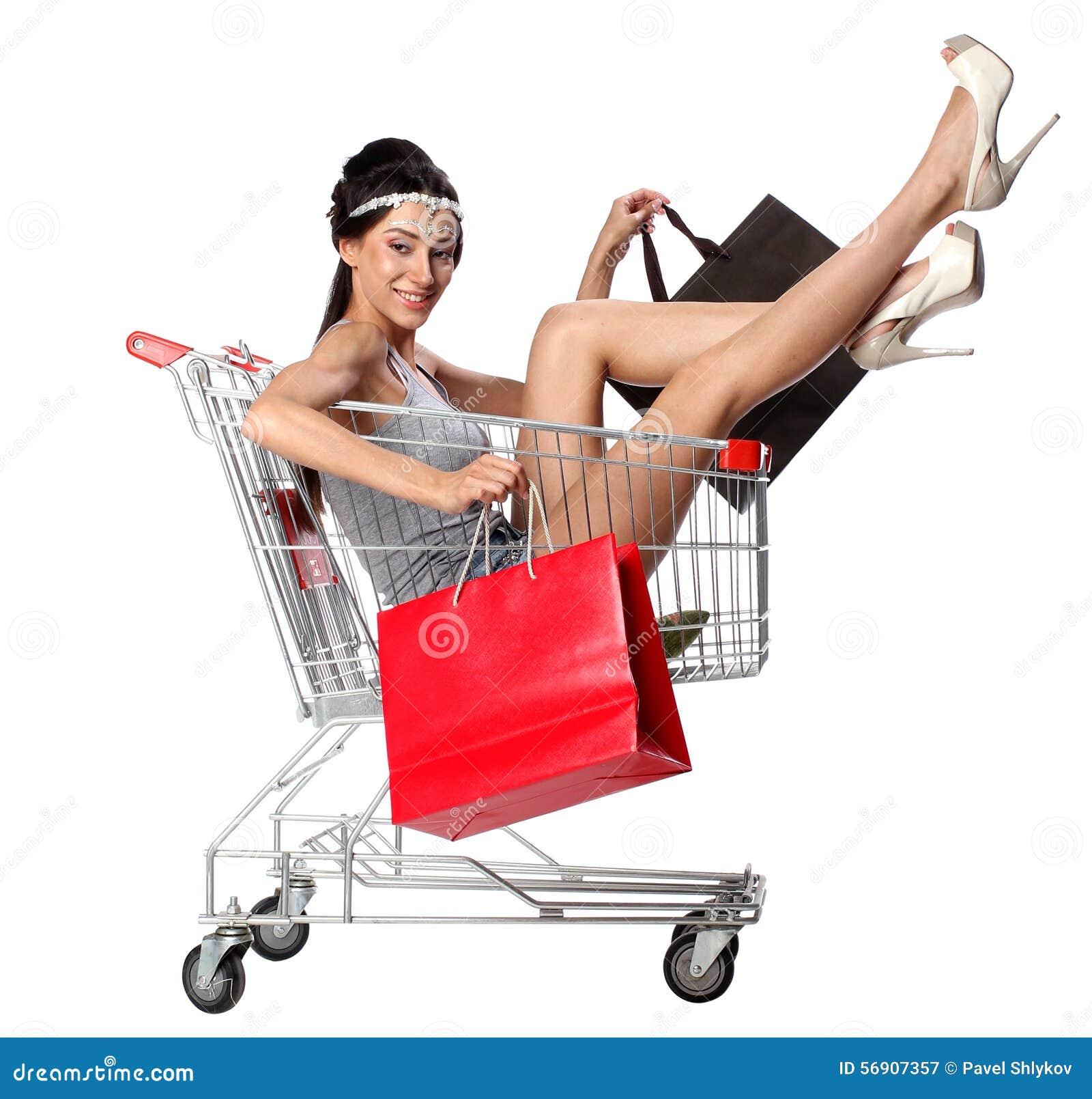 Η όμορφη γυναίκα brunette κάθεται σε ένα κενό καροτσάκι αγορών με το s