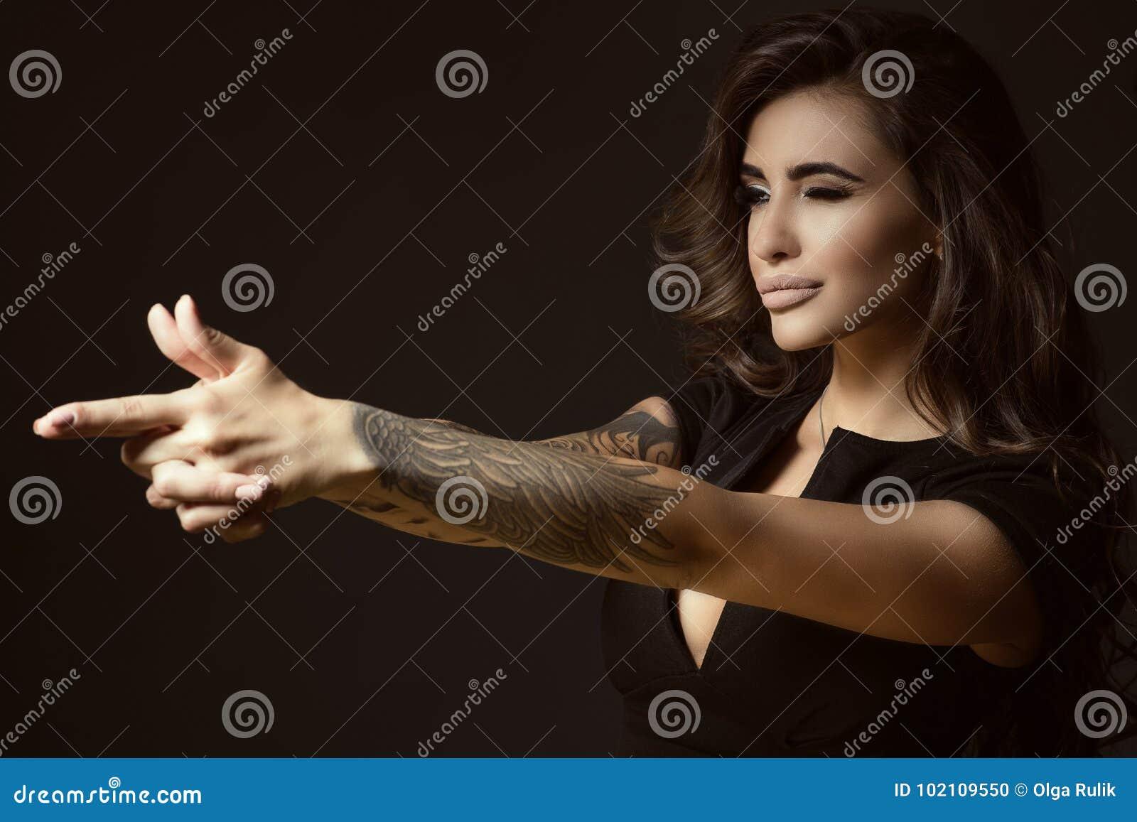 Η όμορφη διαστισμένη γυναίκα με την άφθονη λάμποντας κυματιστή τρίχα και τέλειος αποτελεί την προσποίηση να στοχεύσει κάτι με τη
