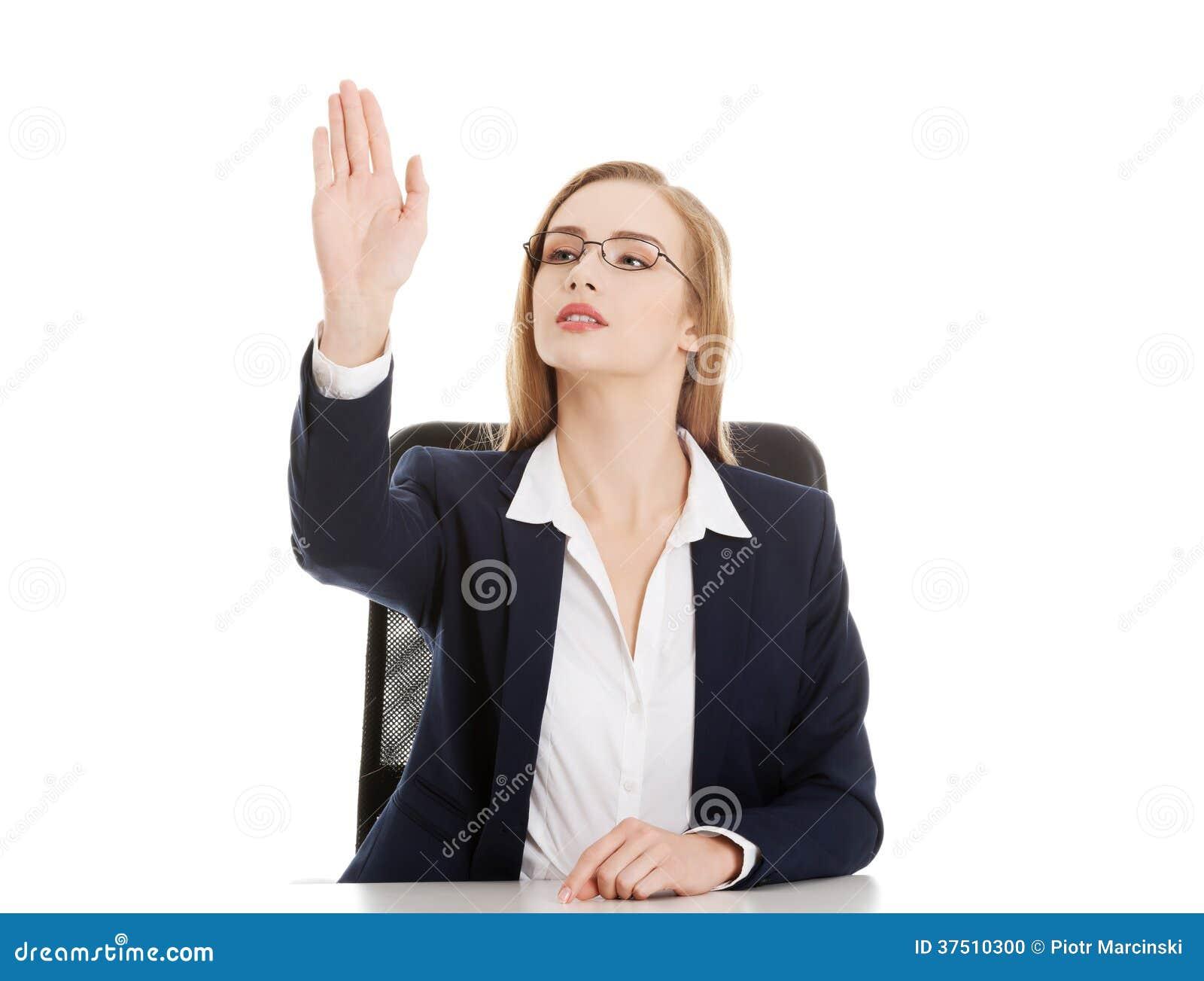 Η όμορφη επιχειρησιακή γυναίκα κάθεται και παρουσιάζει χειρονομία στάσεων.