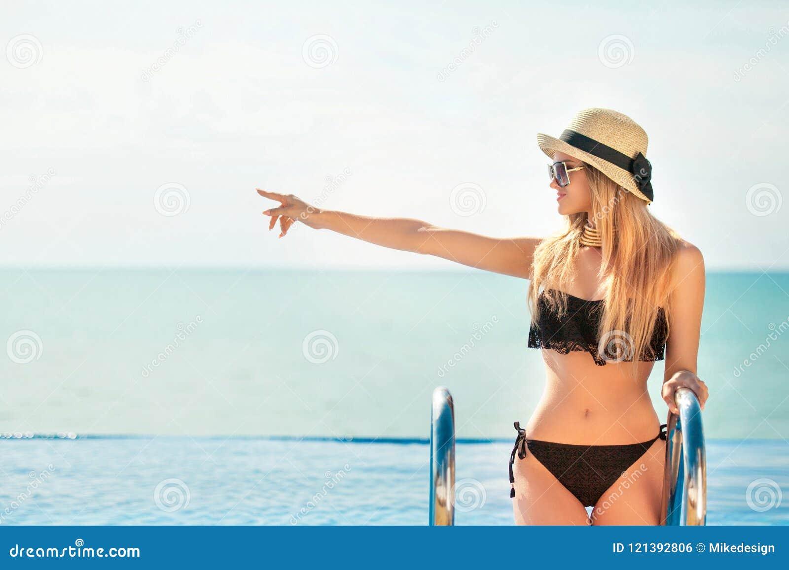 Η όμορφη κατάλληλη γυναίκα στο Μαύρο κολυμπά την τοποθέτηση κοστουμιών και καπέλων στην παραλία krasnodar διακοπές θερινών εδαφών