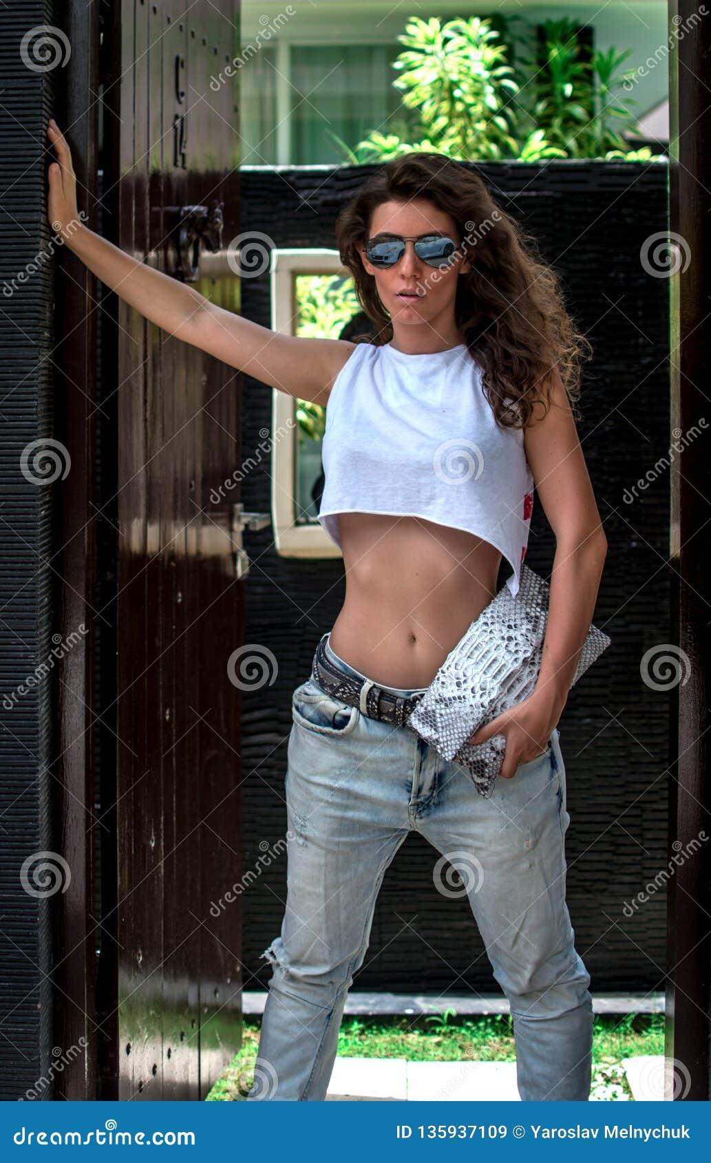Η όμορφη μοντέρνη τοποθέτηση κοριτσιών στην οδό με το όμορφο σώμα είναι κοντά στην ακριβή βίλα Πρότυπα φορώντας μοντέρνα τζιν