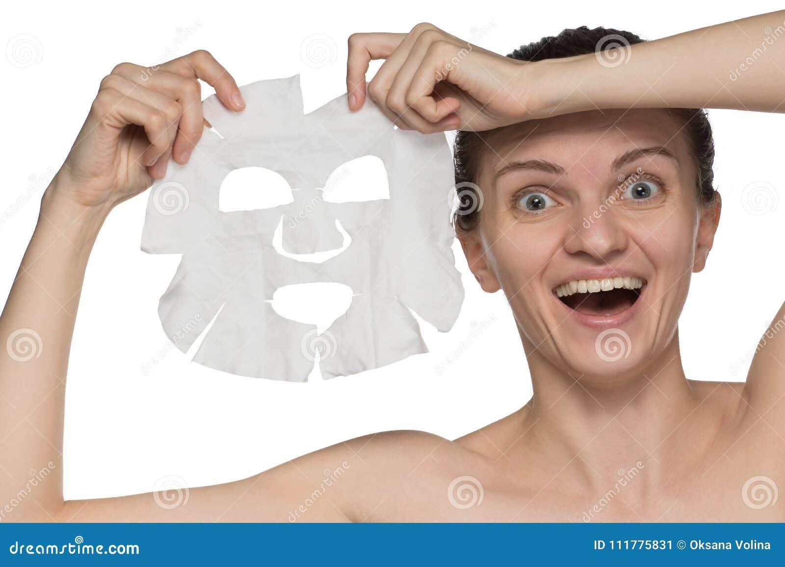 Η όμορφη νέα γυναίκα εφαρμόζει μια καλλυντική μάσκα και χαμογελά επάνω