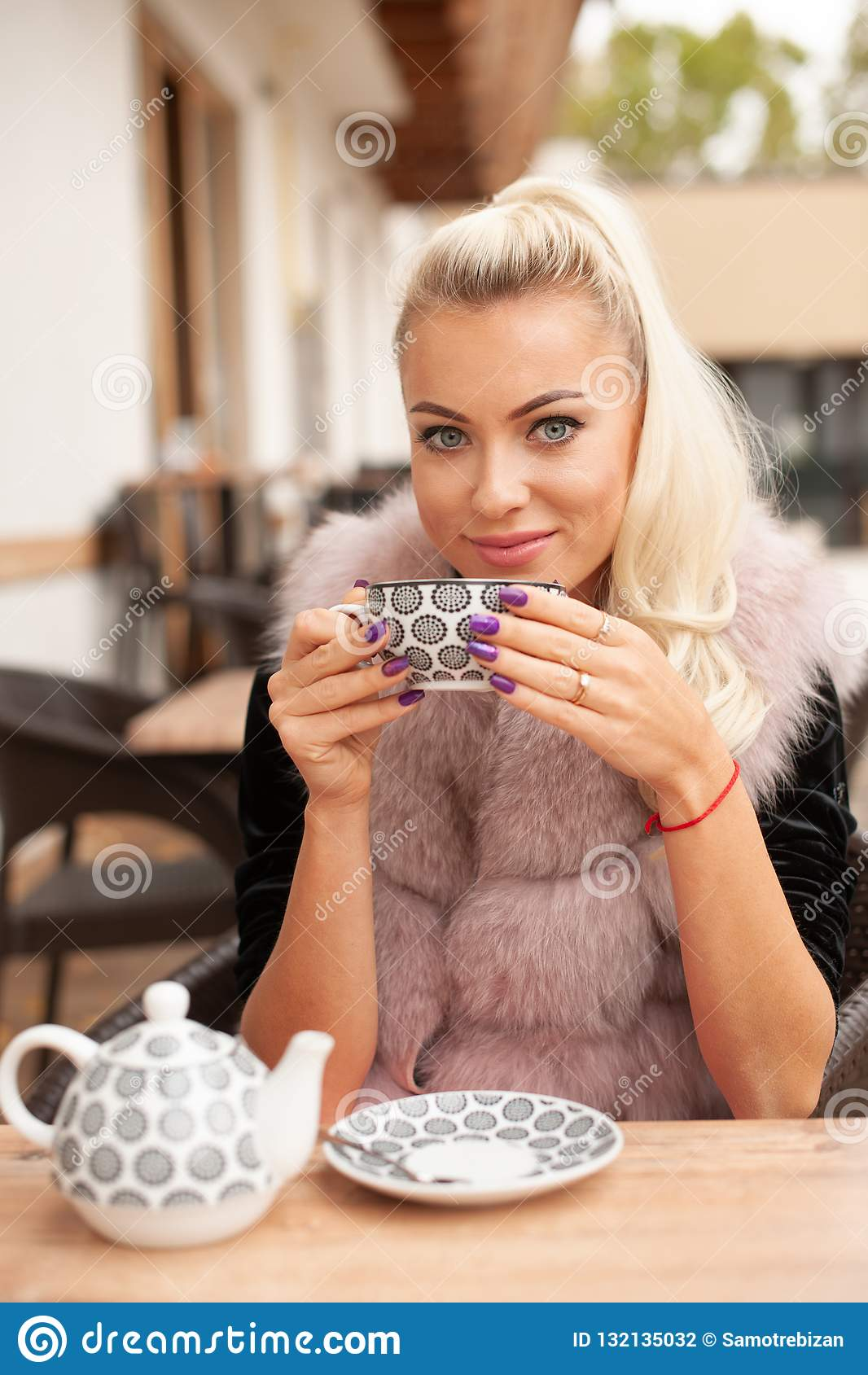 Η όμορφη νέα γυναίκα πίνει το τσάι στο φραγμό terace το πρώιμο φθινόπωρο