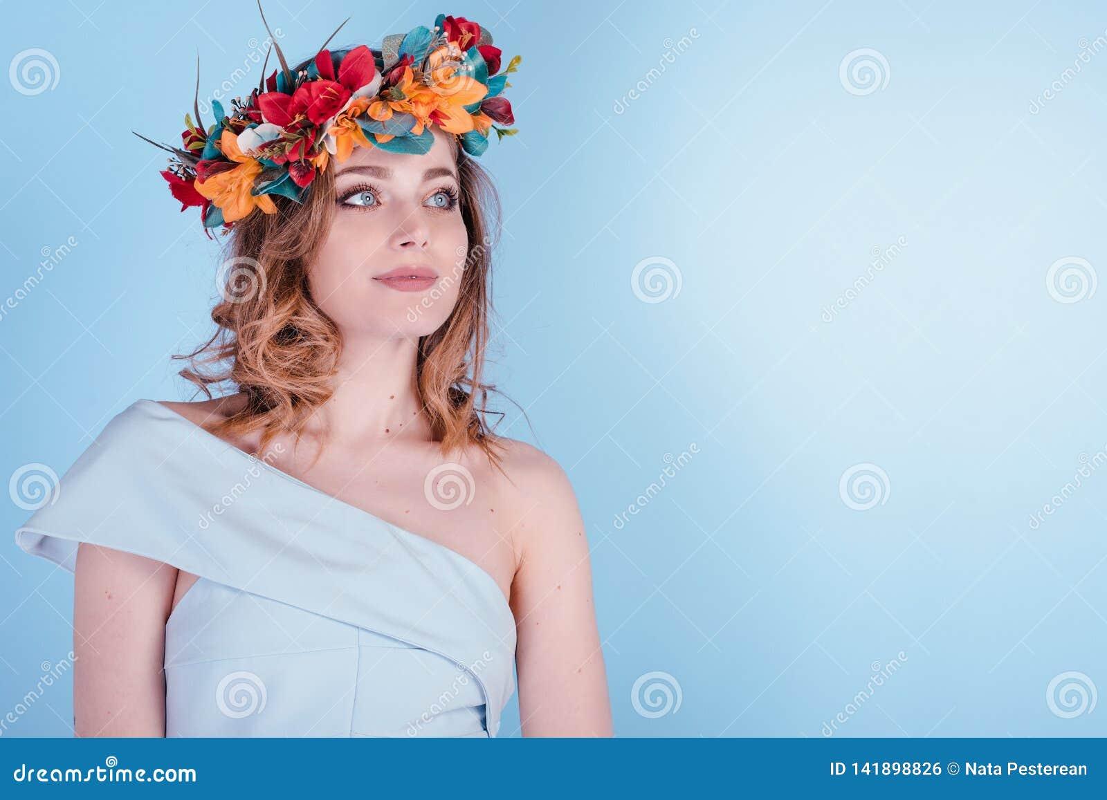 Η όμορφη νέα γυναίκα που φορά τη floral headband κορώνα τιαρών απομόνωσε το ανοικτό μπλε υπόβαθρο, χαμόγελο