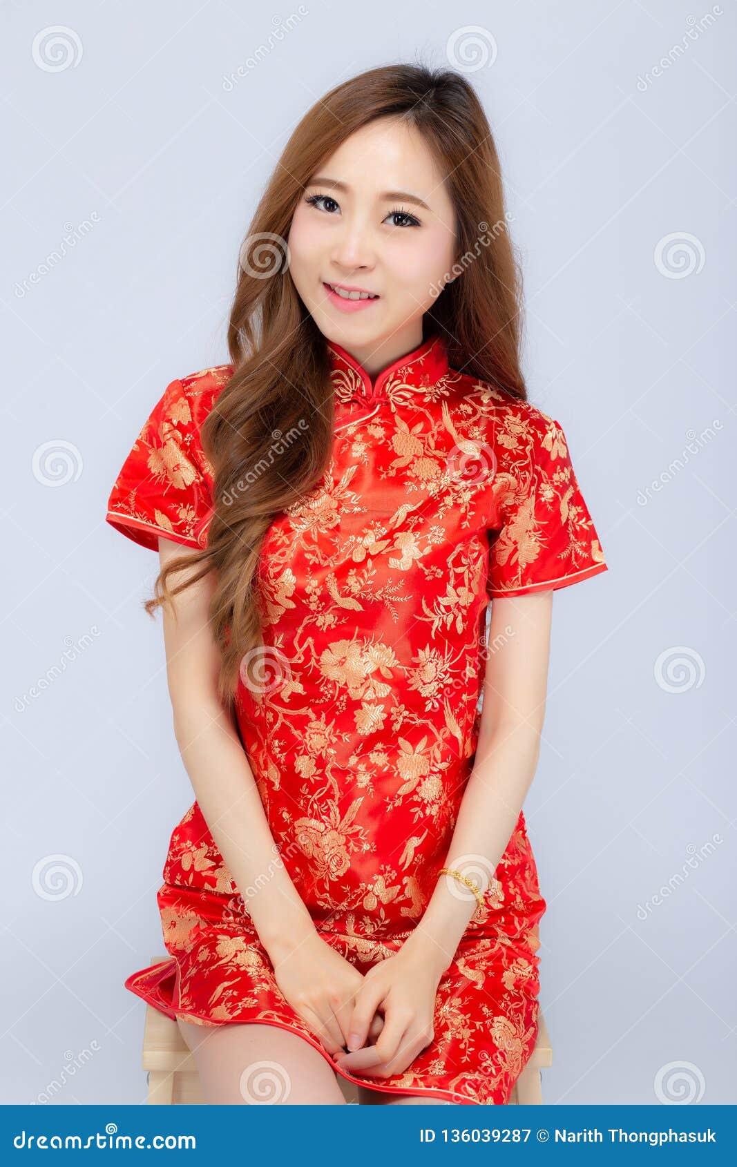 Η όμορφη πορτρέτου ευτυχής κινεζική νέα ένδυση γυναικών έτους νέα ασιατική cheongsam χαμογελά με τα συγχαρητήρια και το χαιρετισμ