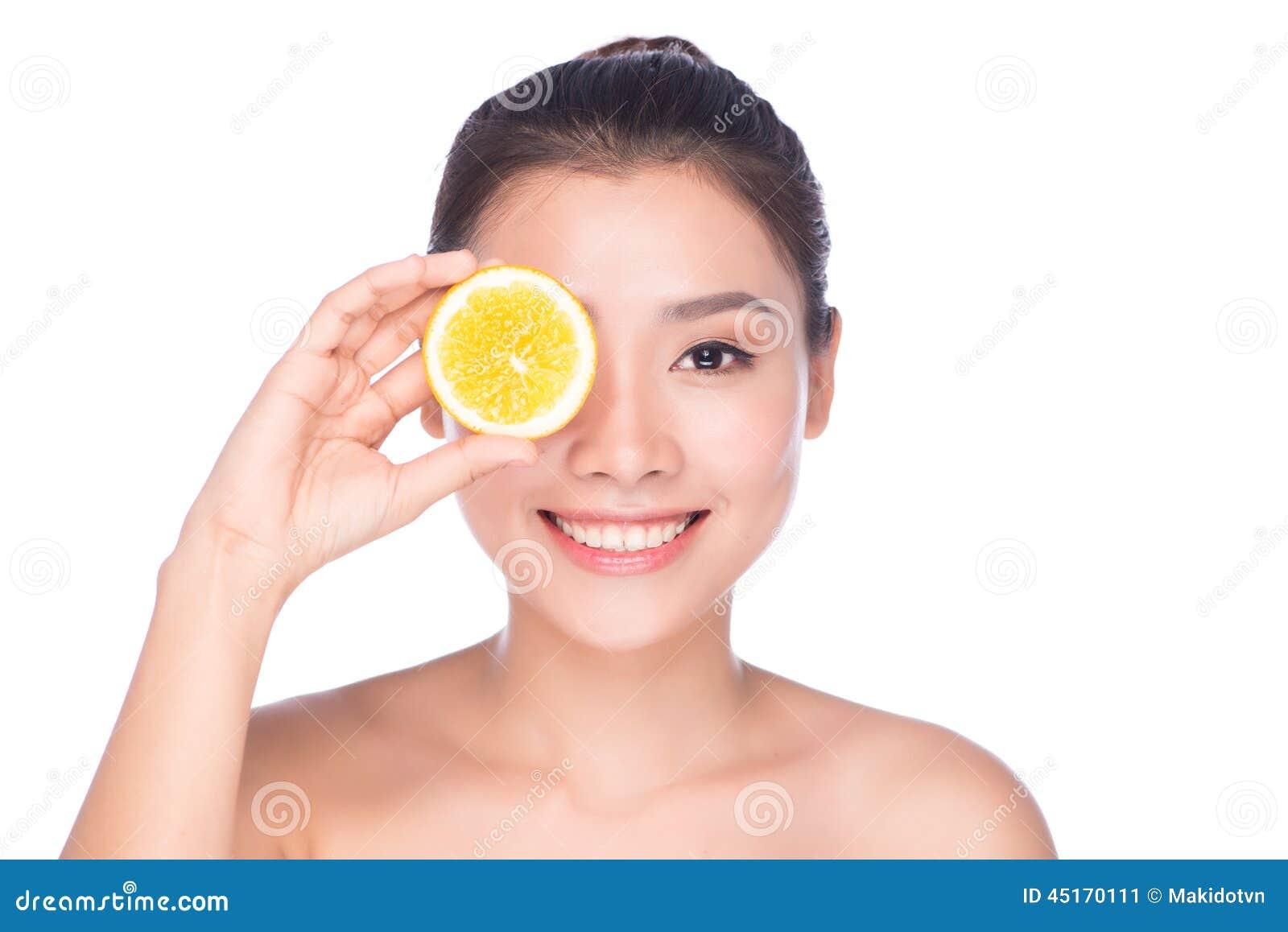 Η όμορφη προκλητική γυναίκα brunette με τα εσπεριδοειδή σε ένα άσπρο υπόβαθρο, υγιή τρόφιμα, νόστιμα τρόφιμα, οργανική διατροφή,