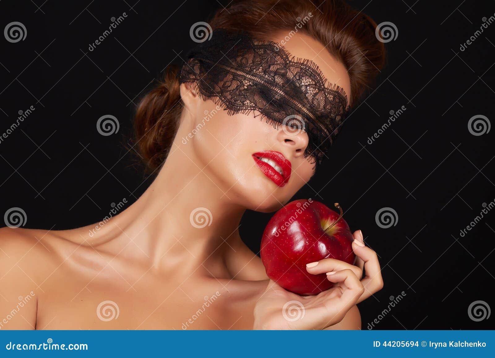 Η όμορφη προκλητική γυναίκα brunette με τη δαντέλλα που τρώει τα κόκκινα υγιή τρόφιμα μήλων, νόστιμα τρόφιμα, οργανική διατροφή,