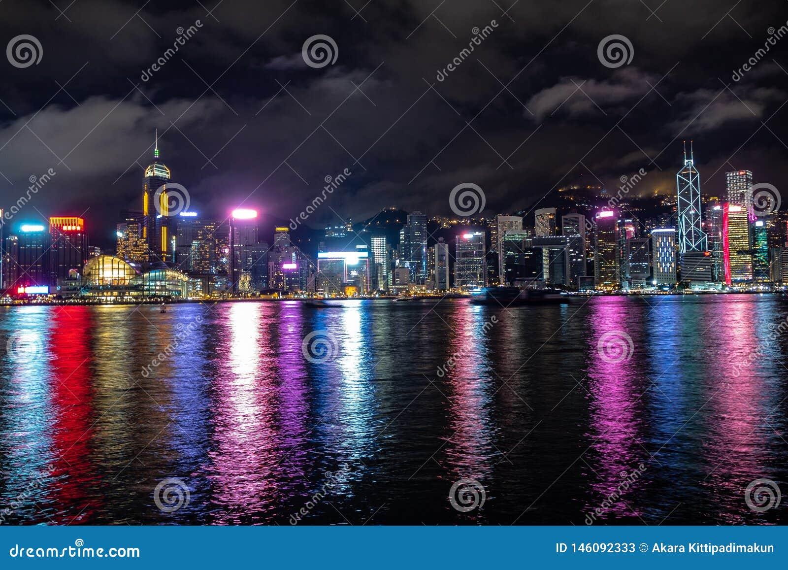Η όμορφη σκηνή πανοράματος της πόλης του Χογκ Κογκ της περιφέρειας του κέντρου τη νύχτα με τους ουρανοξύστες φώτισε την απεικόνισ