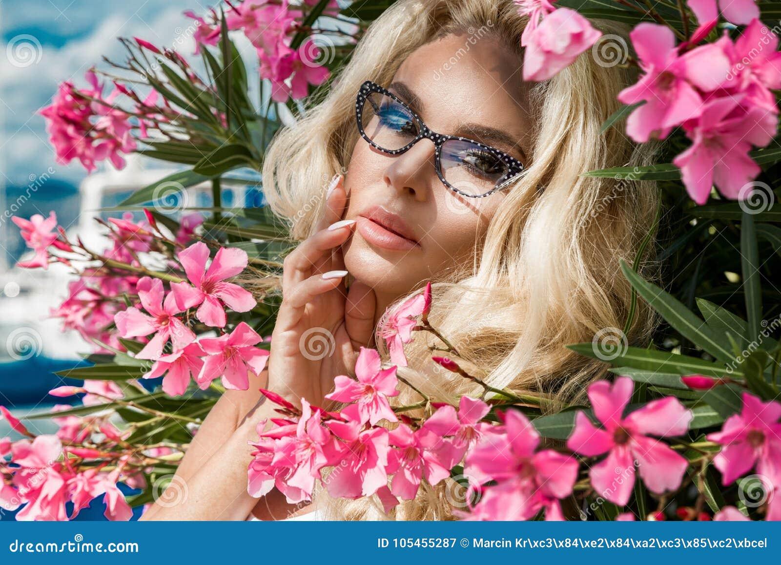 Η όμορφη φαινομενική ζαλίζοντας κομψή προκλητική ξανθή πρότυπη γυναίκα πορτρέτου με την τέλεια φθορά προσώπου γυαλιά στέκεται με