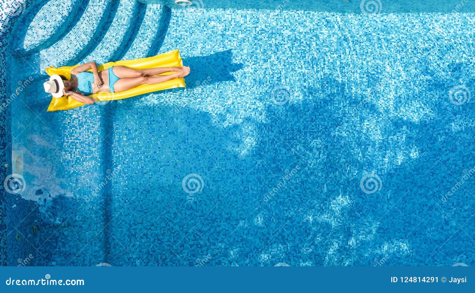 Η όμορφη χαλάρωση νέων κοριτσιών στην πισίνα, κολυμπά στο διογκώσιμο στρώμα και έχει τη διασκέδαση στο νερό στις οικογενειακές δι