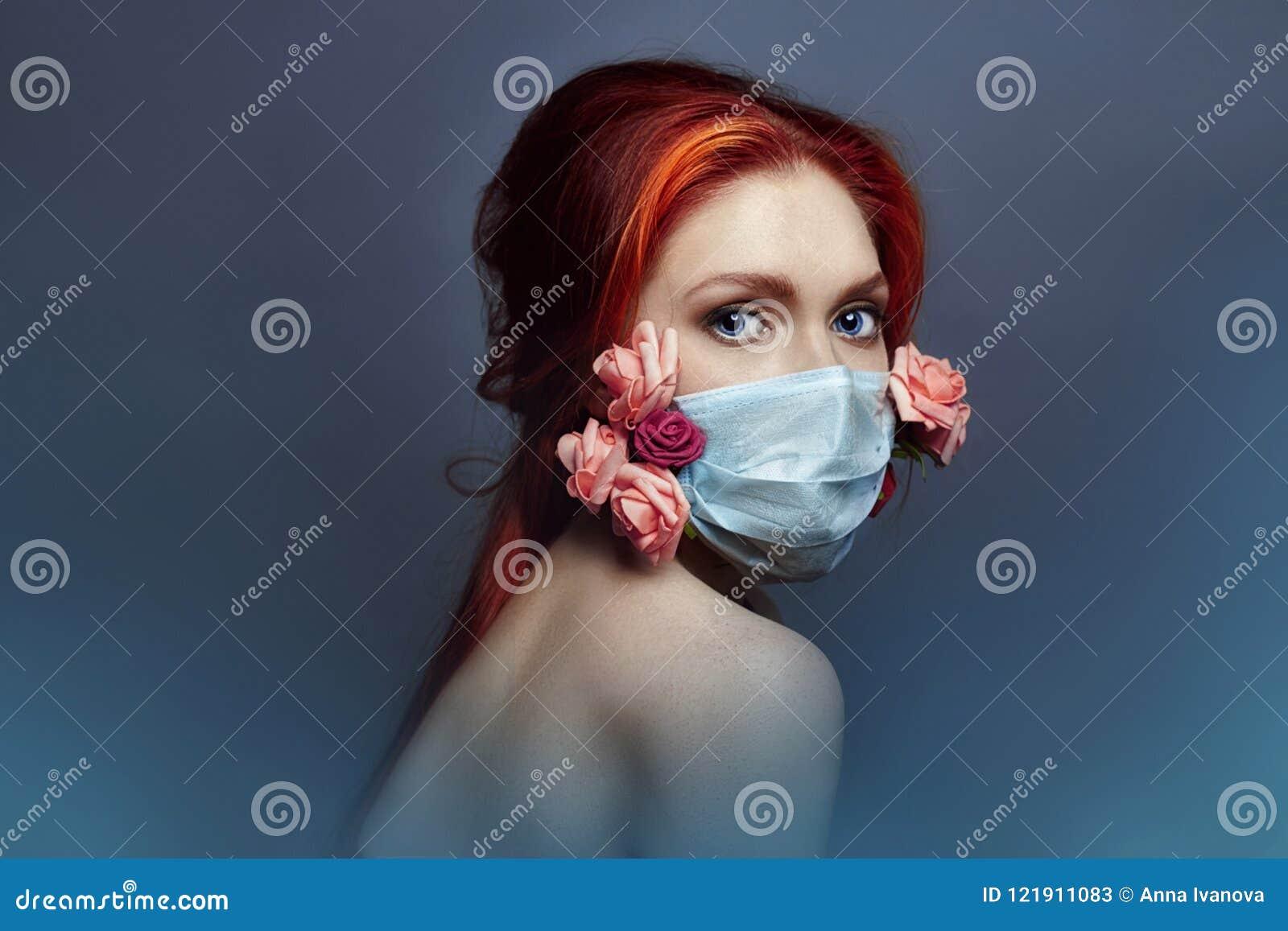 Η redhead γυναίκα μόδας τέχνης με την ιατρική αναπνευστική συσκευή στο πρόσωπό της, αυξήθηκε λουλούδια αυξάνεται από κάτω από τη