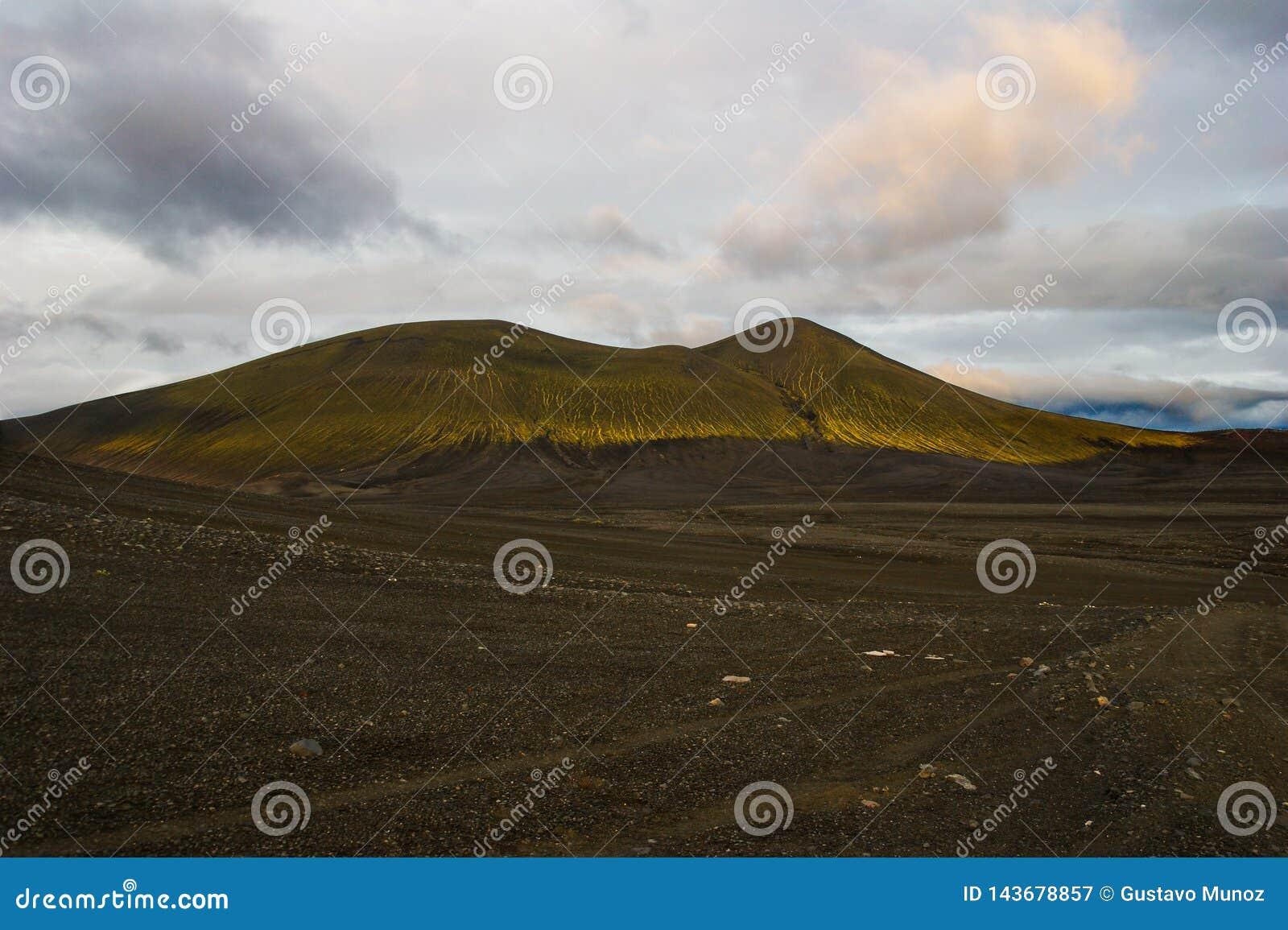 Θαυμάσιο ηφαιστειακό τοπίο στο δρόμο σε Landmannalaugar, Ισλανδία Μαύρη ηφαιστειακή τέφρα που καλύπτεται από τα πράσινα βρύα