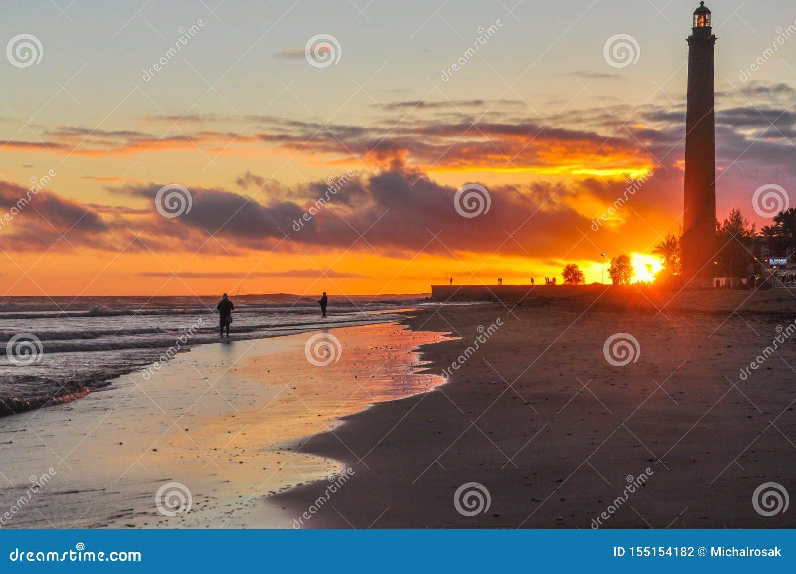 Θεαματικό ηλιοβασίλεμα στην παραλία Maspalomas στους εθνικούς αμμόλοφους πάρκων και άμμου Ψαράδες και διάσημος φάρος στη νότια αι